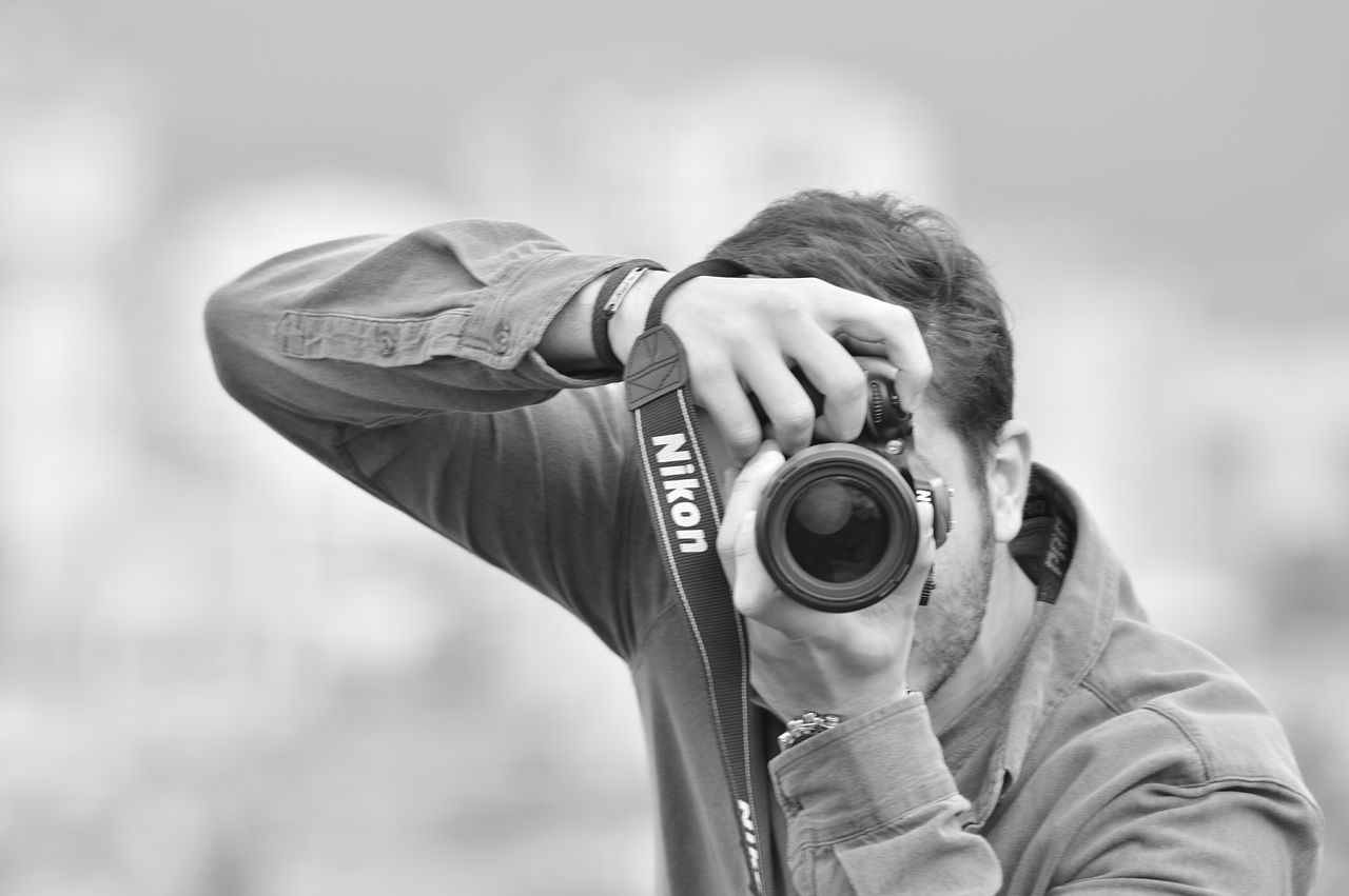 real people, camera - photographic equipment, photography themes, one person, focus on foreground, photographing, digital camera, leisure activity, photographer, outdoors, technology, men, digital single-lens reflex camera, holding, day, headshot, camera, lifestyles, slr camera, close-up