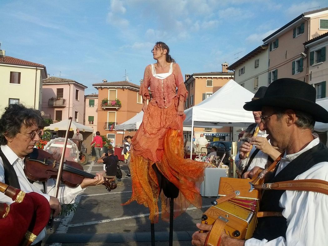 Street Artists, ladyOn Stilts among Street Musicians, FeastDay in Calmasino near gardalake.