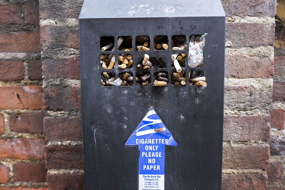 A cigarette disposal unit fitted to a brick wall. This image records the ashtray is full. In Europe smoking is banned from the inside of public and business premises so smokers are forced to smoke outside. Addicted Addiction Arrow Ash Ashtray  Break Breaktime Brick Wall Bricks Cigarette  Cigarettes Dirty Discarded Disgusting  Full Fumes Metal No People Outdoor Photography Outdoors Outside Point Pointing Smoking Wall