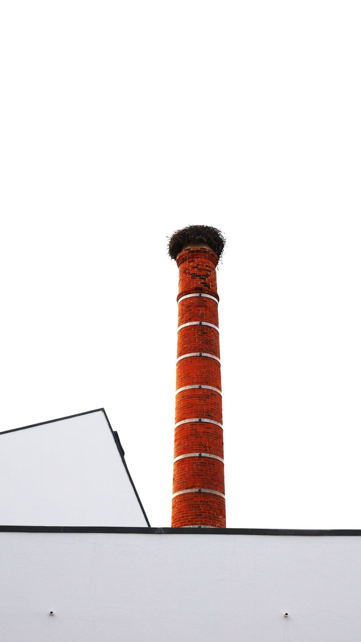 Low Angle View Of Nest On Top Of Smoke Stack Against Clear Sky