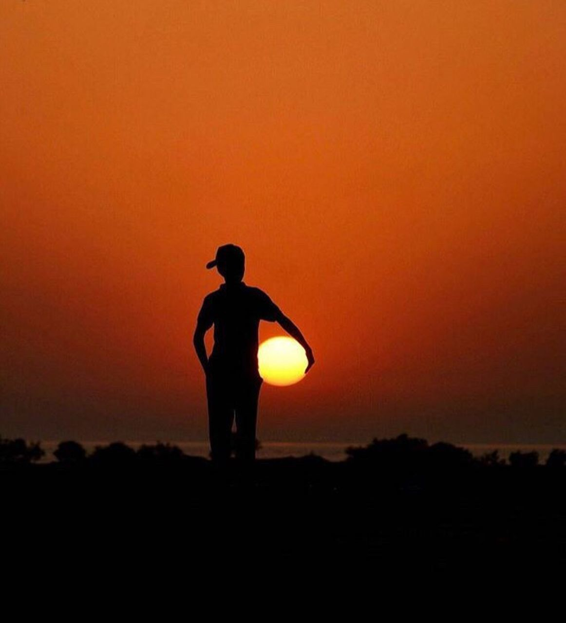 sunset, silhouette, orange color, standing, nature, outdoors, tranquility, scenics, one person, beauty in nature, tranquil scene, real people, leisure activity, men, sky, one man only, full length, adult, only men, adults only, people, day
