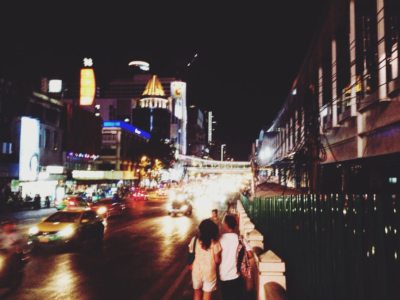 night, building exterior, architecture, built structure, illuminated, city, togetherness, city life, real people, blurred motion, women, outdoors, lifestyles, men, cityscape, sky, people