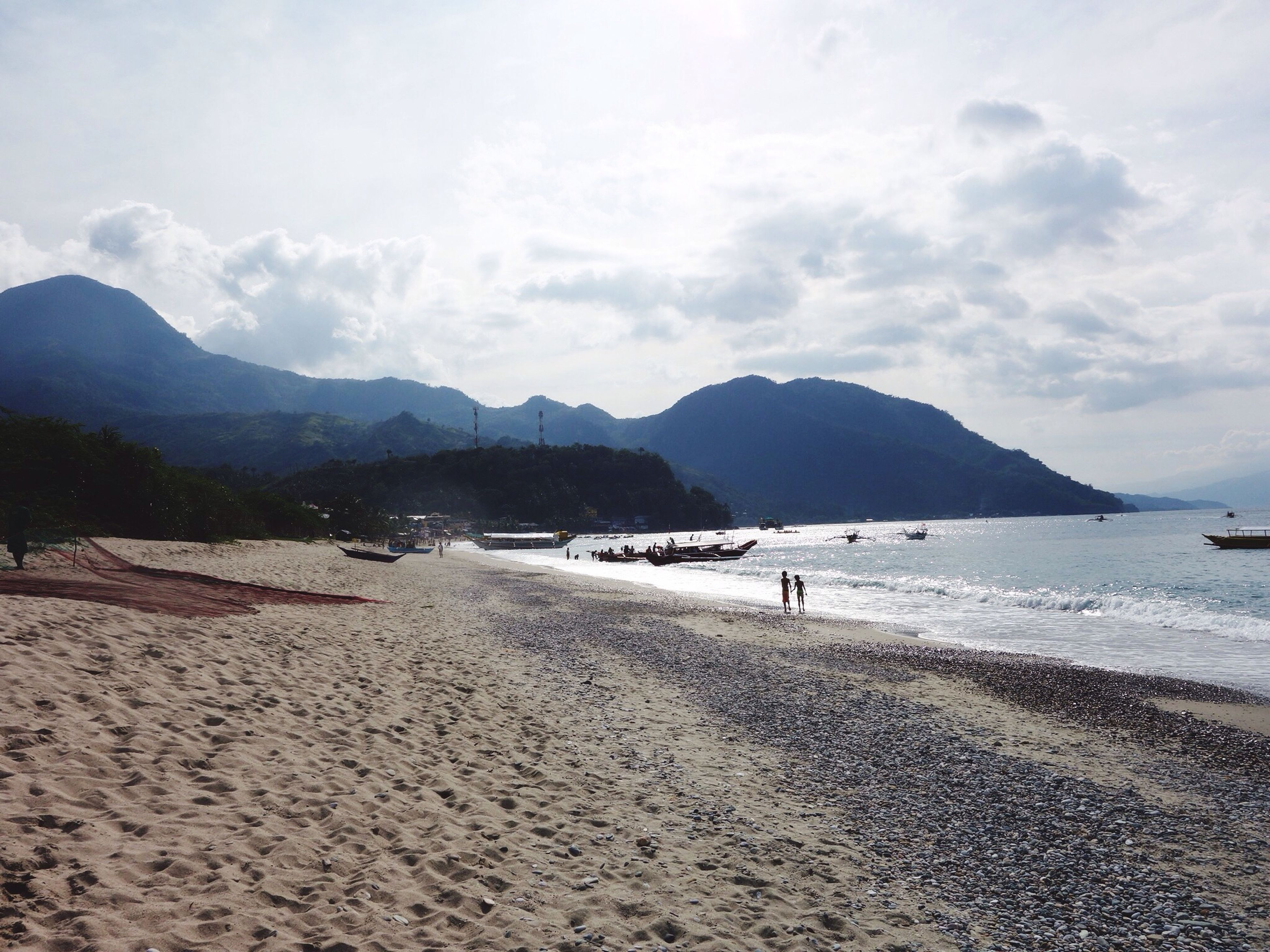 beach, sea, sky, water, mountain, sand, shore, scenics, tranquil scene, beauty in nature, tranquility, cloud - sky, nature, incidental people, coastline, cloud, vacations, mountain range, walking