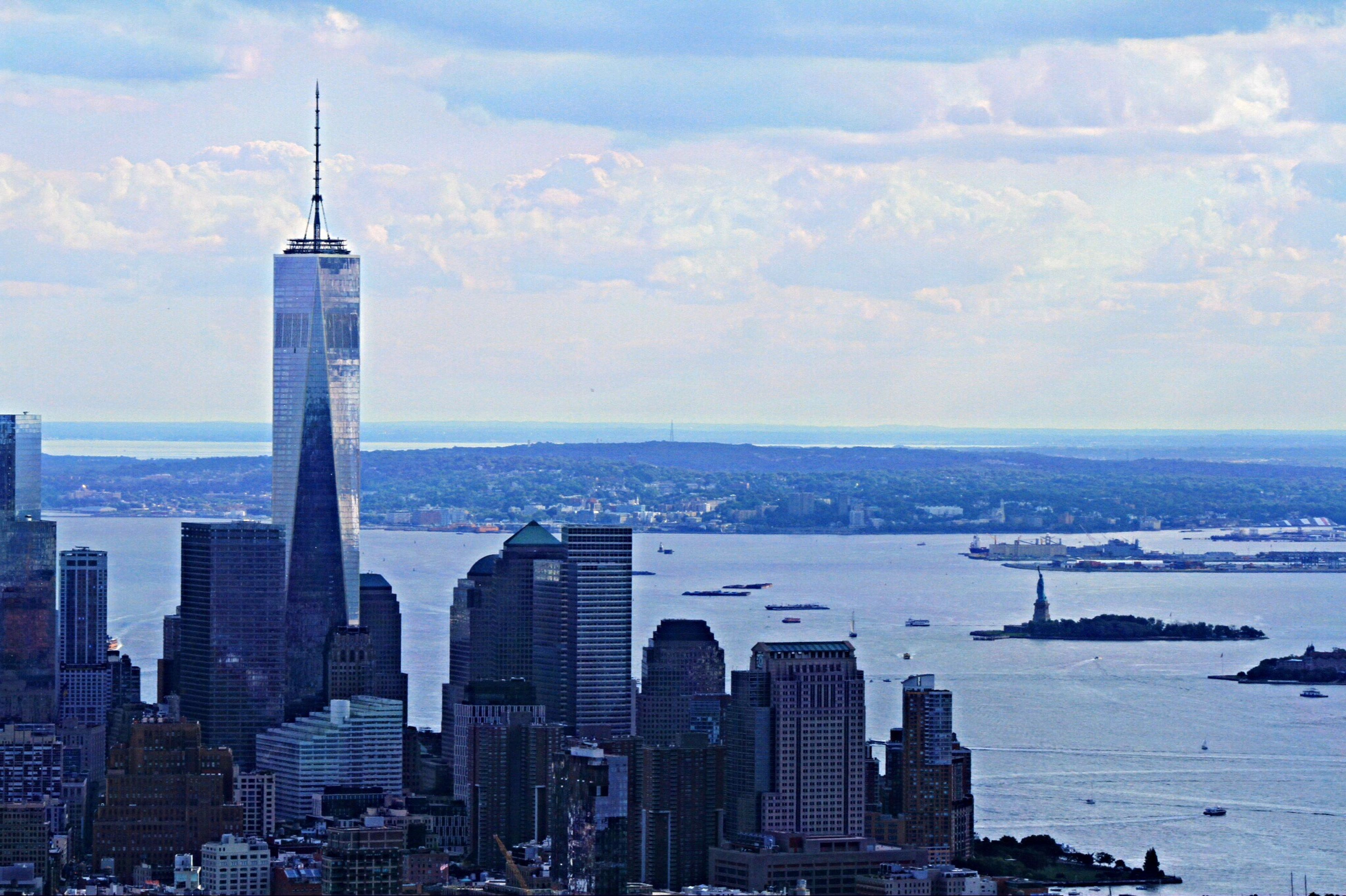 building exterior, architecture, city, skyscraper, built structure, tower, tall - high, cityscape, sea, sky, modern, water, office building, capital cities, financial district, urban skyline, travel destinations, cloud - sky, travel, famous place