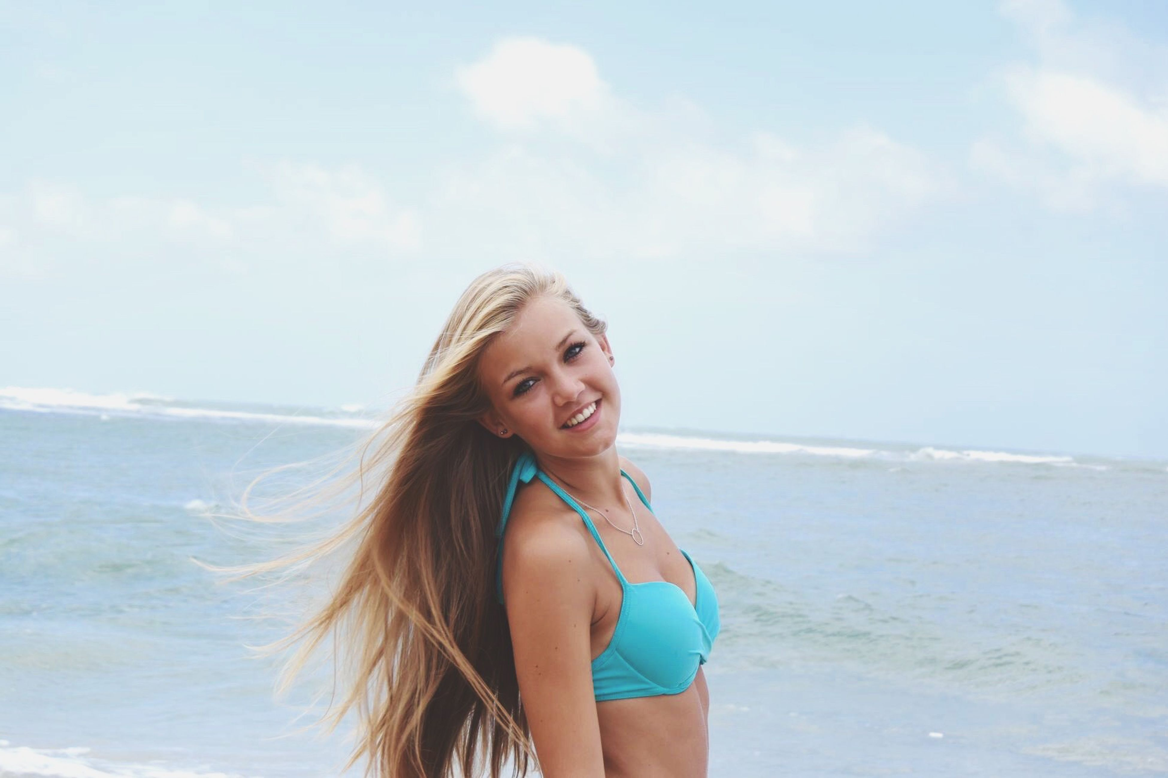 sea, young adult, person, beach, young women, water, portrait, looking at camera, lifestyles, leisure activity, smiling, long hair, happiness, sky, vacations, front view, sunglasses