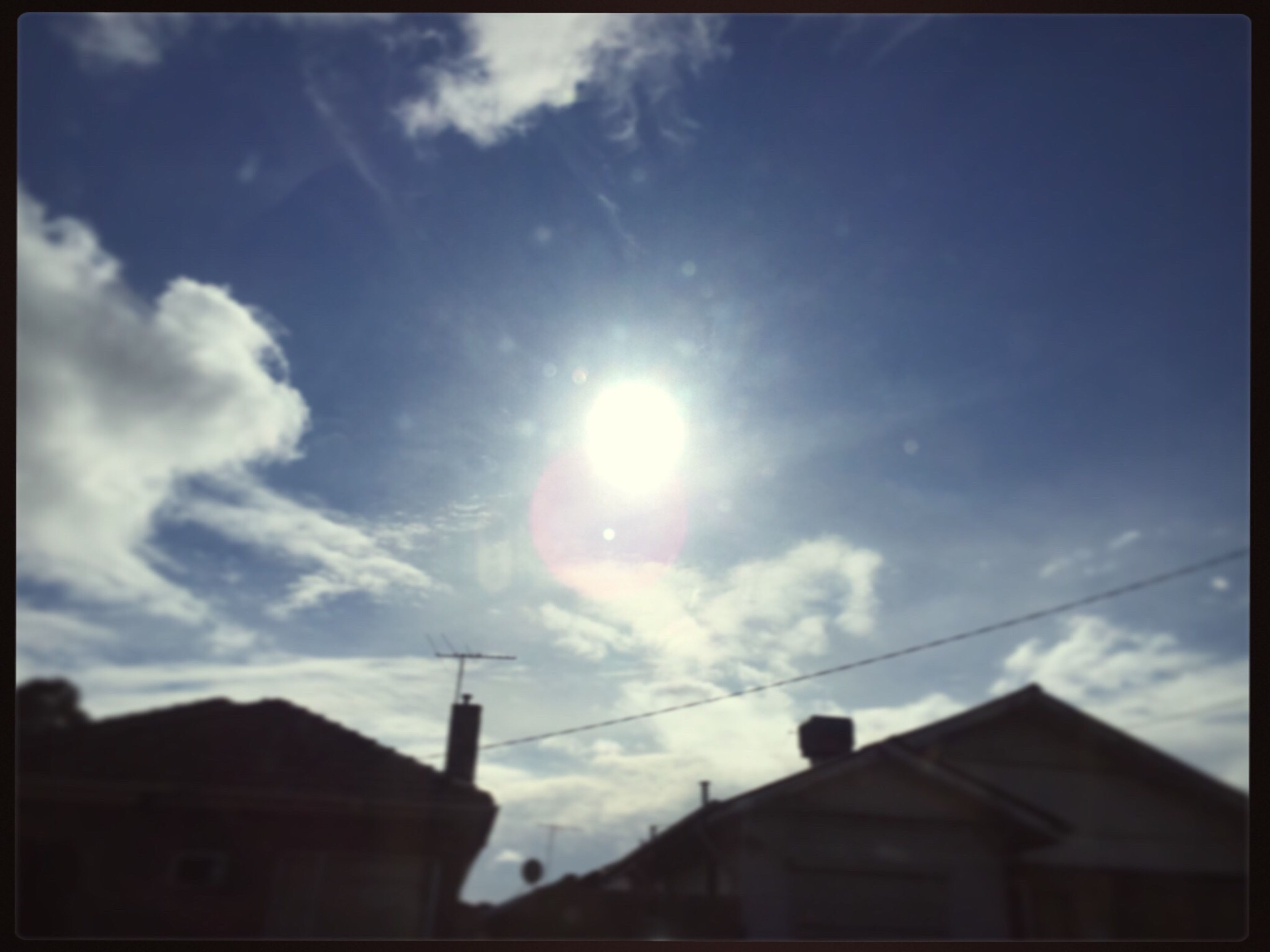 building exterior, architecture, built structure, sun, sky, low angle view, sunlight, sunbeam, lens flare, cloud - sky, cloud, high section, building, outdoors, blue, day, no people, city, sunny, nature, cloudy, bright, weather, beauty in nature