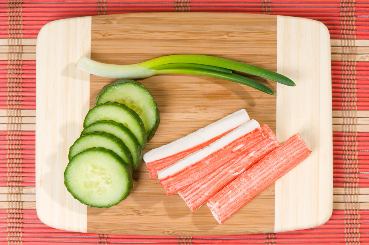 Crab sticks of surimi and cucumber with chives, objects lying on wooden chopping board on red mat in horizontal orientation, nobody. Chive Chives Chopping Board Crab Crab Stick Crab Sticks Cucumber Cucumis Fish Food Imitation Meat No People Seafood Stick Sticks Surimi Trencher Vegetable White Meat