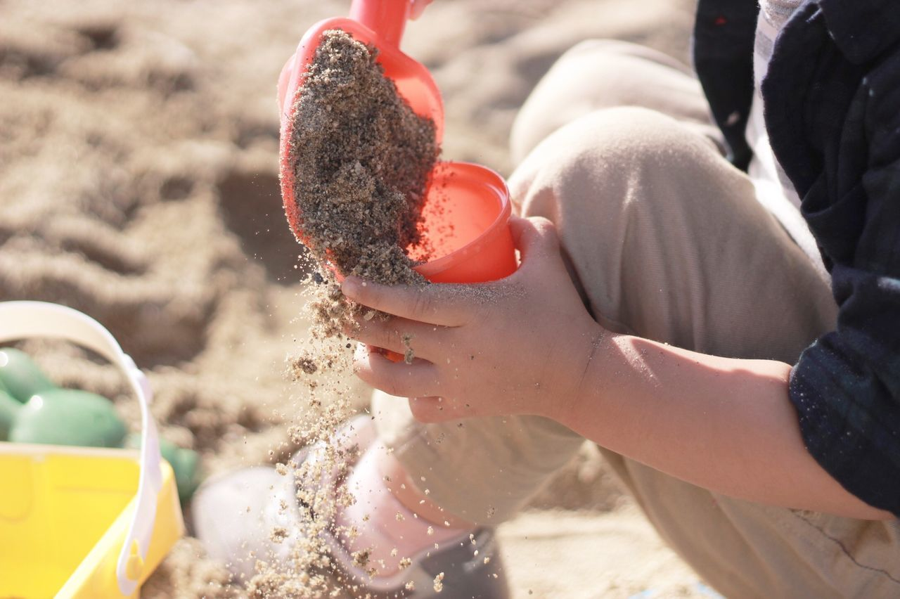 Sand Pail And Shovel Sandpit Childhood Lifestyles Human Hand Childhand Real People One Person Day Playing Outdoors Leisure Activity Sunlight Holding High Angle View Boys Water Fun Low Section Human Body Part Motion Close-up Japan