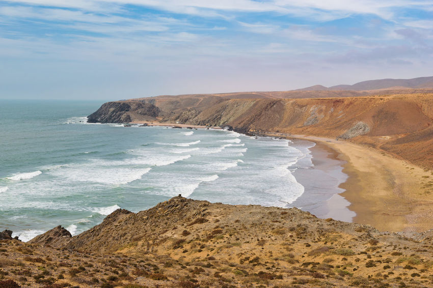 Panoramic colorful coastline with a view over a small bay with a few fishing lodges at the Atlantic Ocean near Sidi Ifni in Morooco, Africa Atlantic Atlantic Ocean Coastline Morocco Nature Sunny Wave Bay Beach Coast Fishing Horizon Over Water Lodge Nature No People Outdoors Sand Scenics Sea Shore Sky Souss Souss Massa Tranquil Scene Water