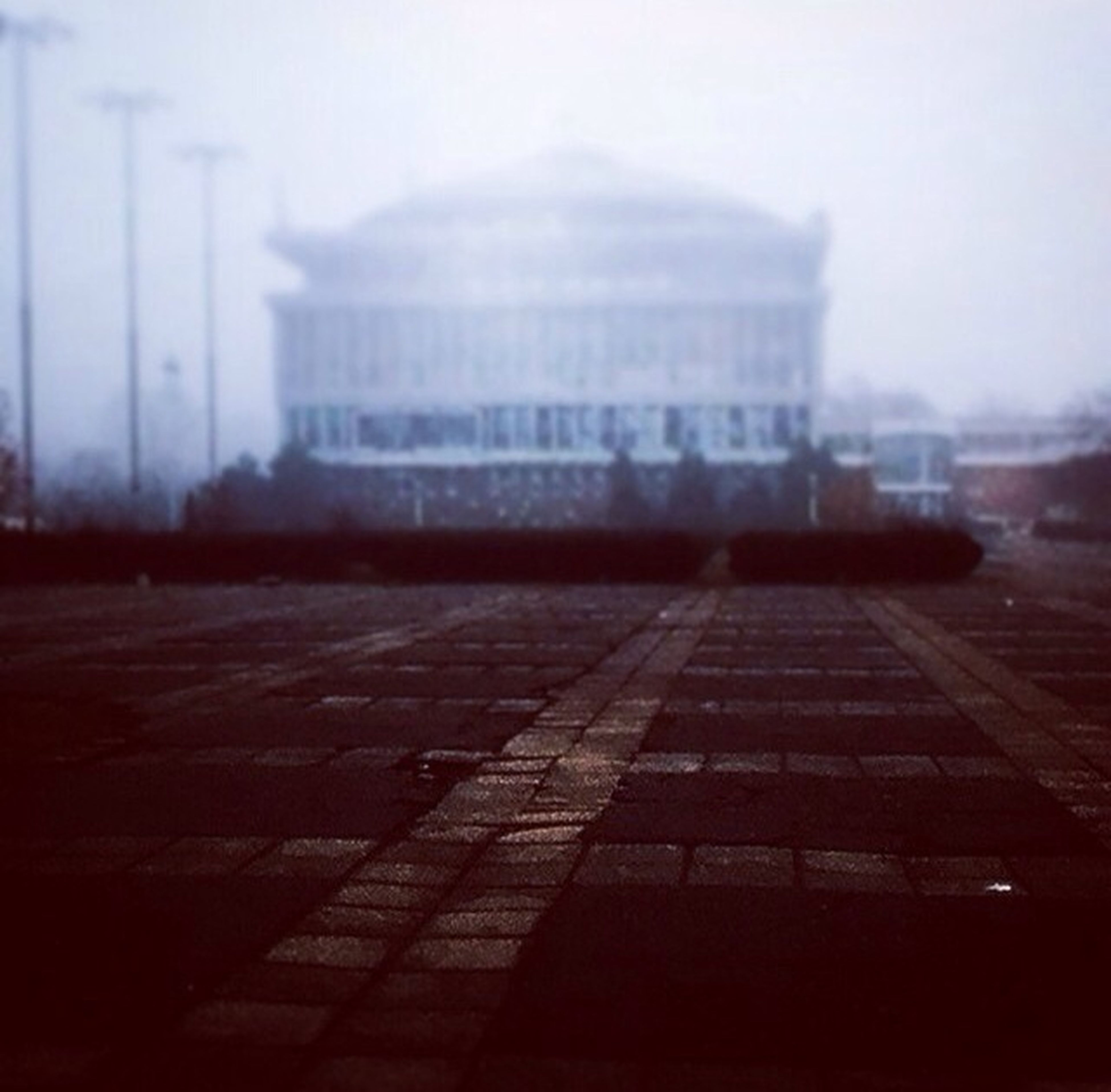 architecture, built structure, building exterior, transportation, city, the way forward, street, sky, surface level, road, empty, fog, outdoors, weather, no people, day, focus on foreground, diminishing perspective, building, selective focus
