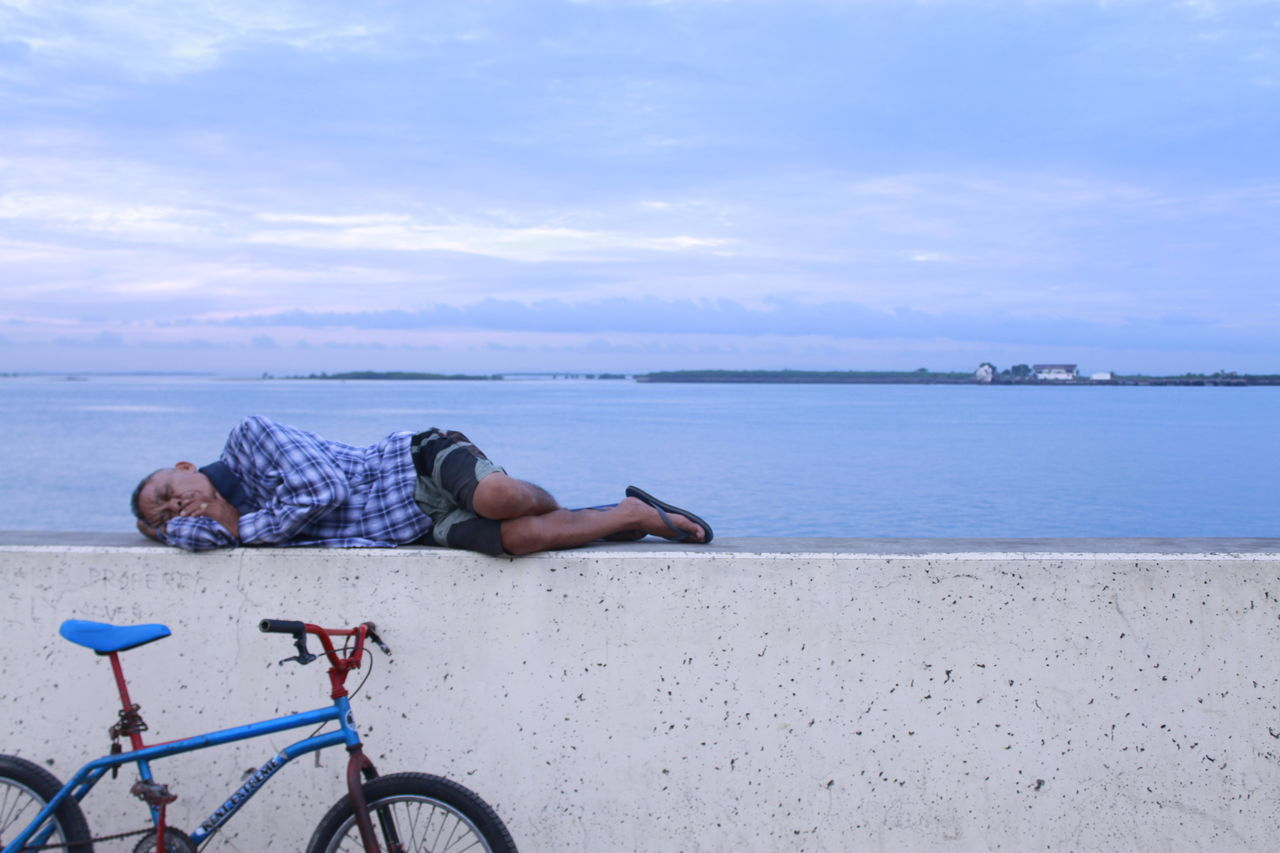 Cebu City A Child's Bike Beauty In Nature Beggar Sleeping By The Sea Calm Cloud Cloud - Sky Day Horizon Over Water Leisure Activity Lifestyles Lying Down Nature Relaxation Resting Resting And Relaxing Scenics Sea Shore Sitting Sky Sleeping Man Tranquil Scene Tranquility Vacations Water