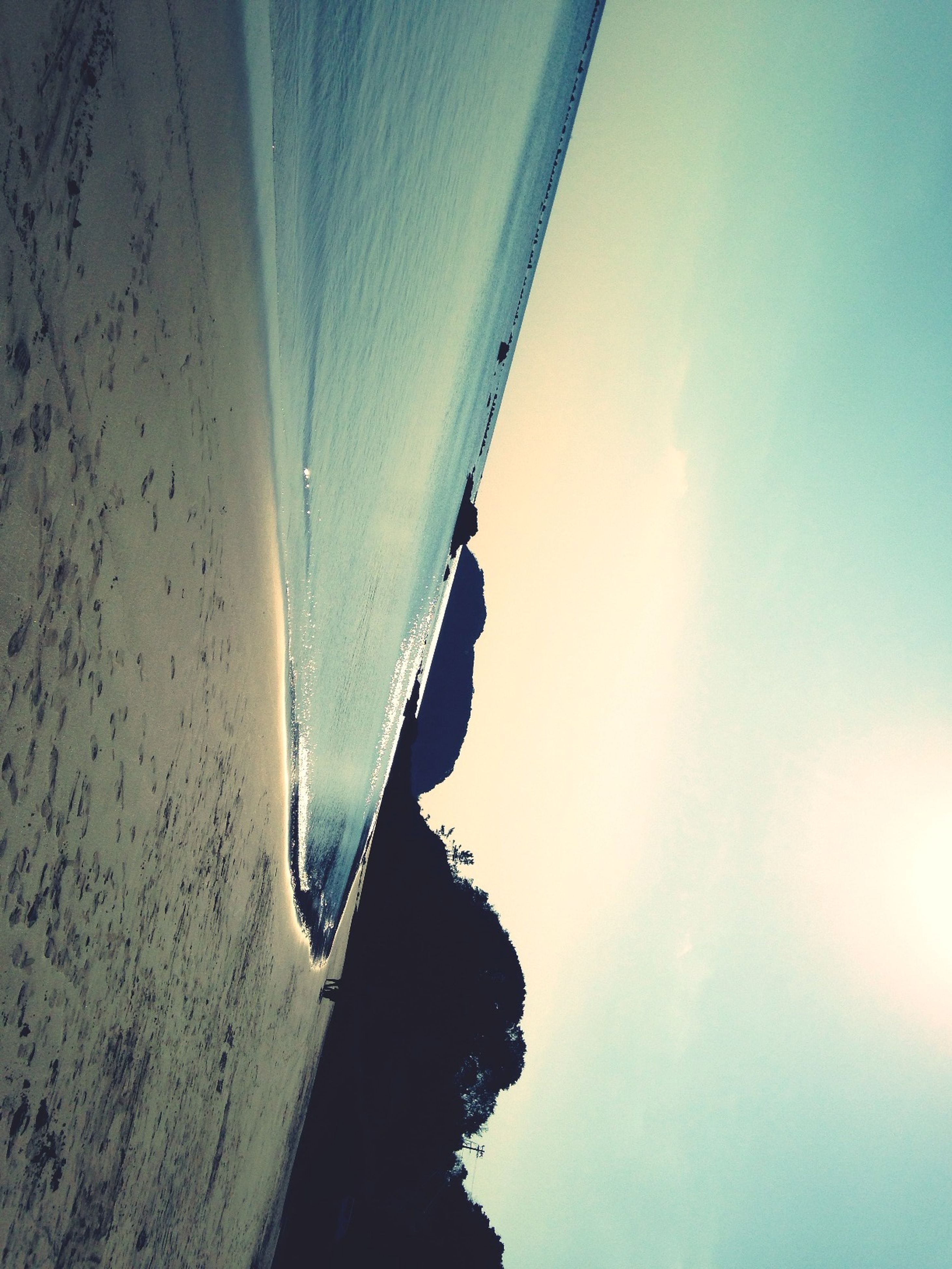 sea, beach, water, scenics, tranquil scene, beauty in nature, tranquility, shore, sand, sky, nature, horizon over water, mountain, coastline, idyllic, wave, vacations, blue, sunlight, surf