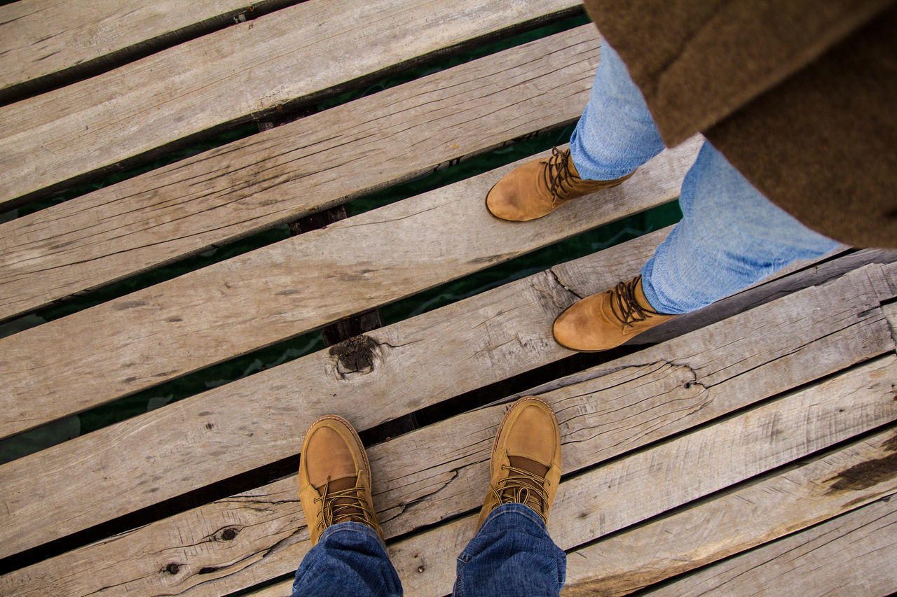 low section, wood - material, shoe, human leg, standing, human body part, jeans, casual clothing, real people, day, one person, outdoors, high angle view, lifestyles, men, leisure activity, close-up, people, adult, adults only