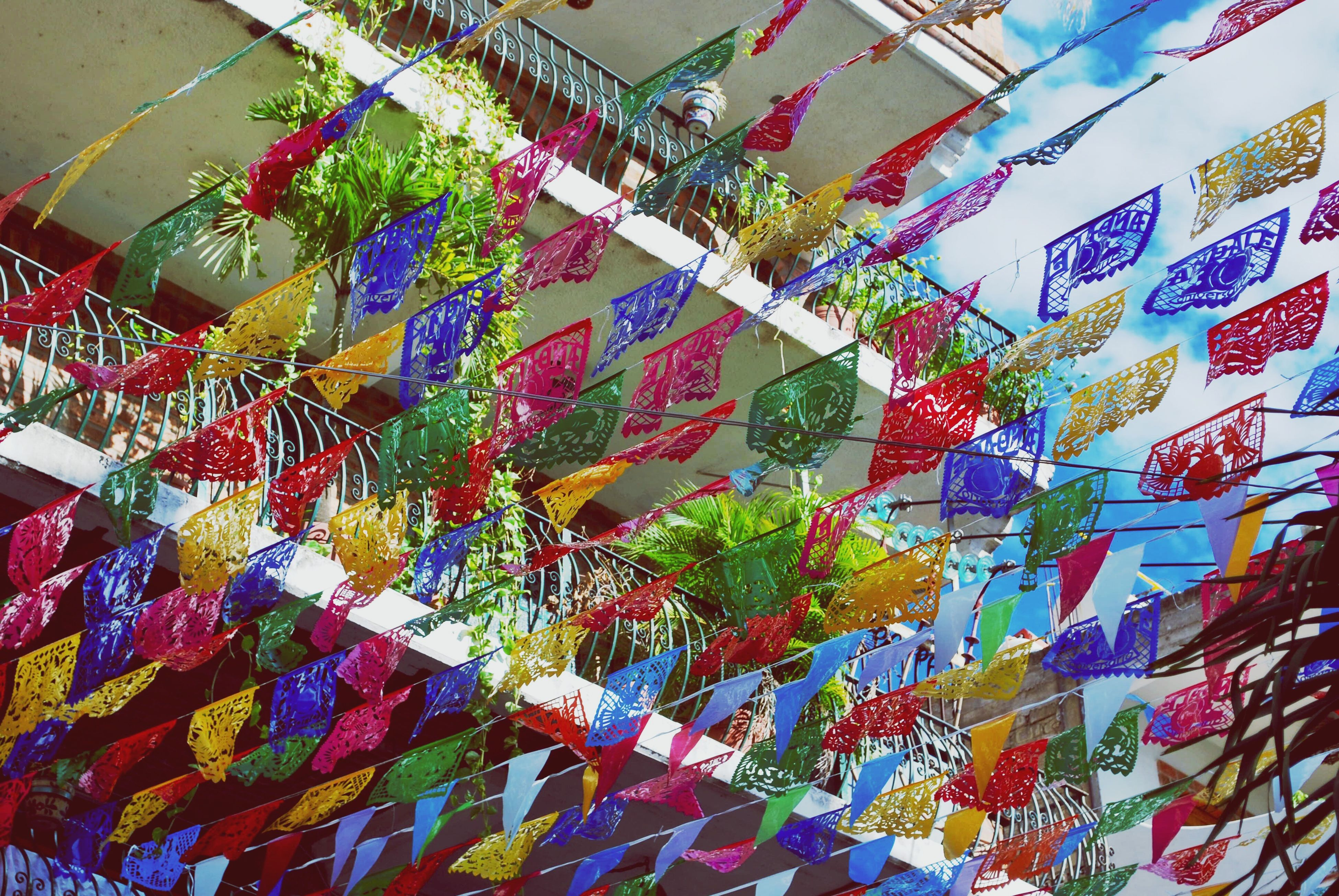 multi colored, low angle view, decoration, in a row, hanging, variation, architecture, colorful, built structure, building exterior, large group of objects, sky, day, growth, no people, outdoors, abundance, creativity, vibrant color, full frame, decorated