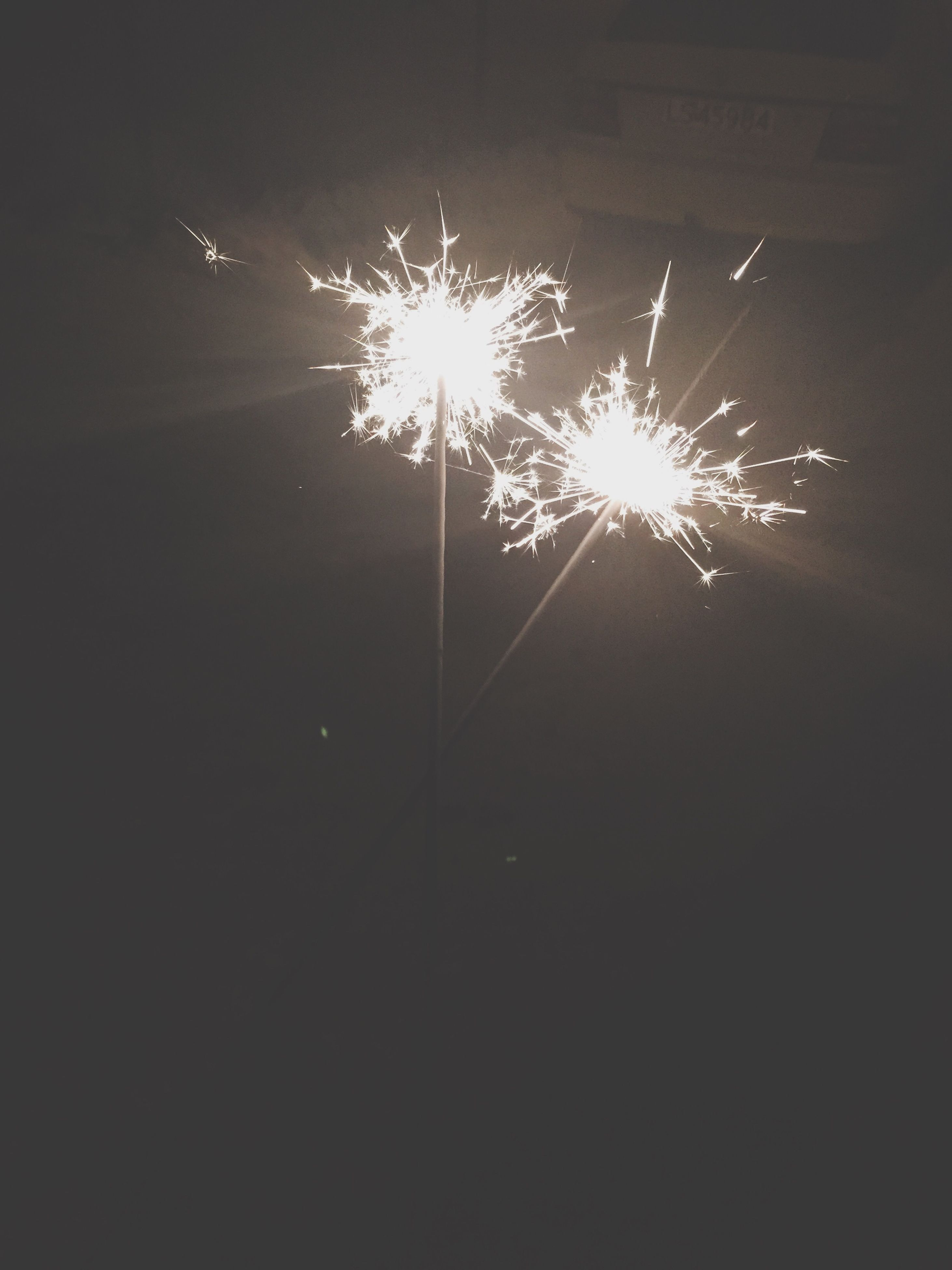 night, illuminated, firework display, exploding, celebration, firework - man made object, glowing, long exposure, sparks, arts culture and entertainment, motion, low angle view, firework, event, fire - natural phenomenon, blurred motion, entertainment, sky, outdoors, light - natural phenomenon