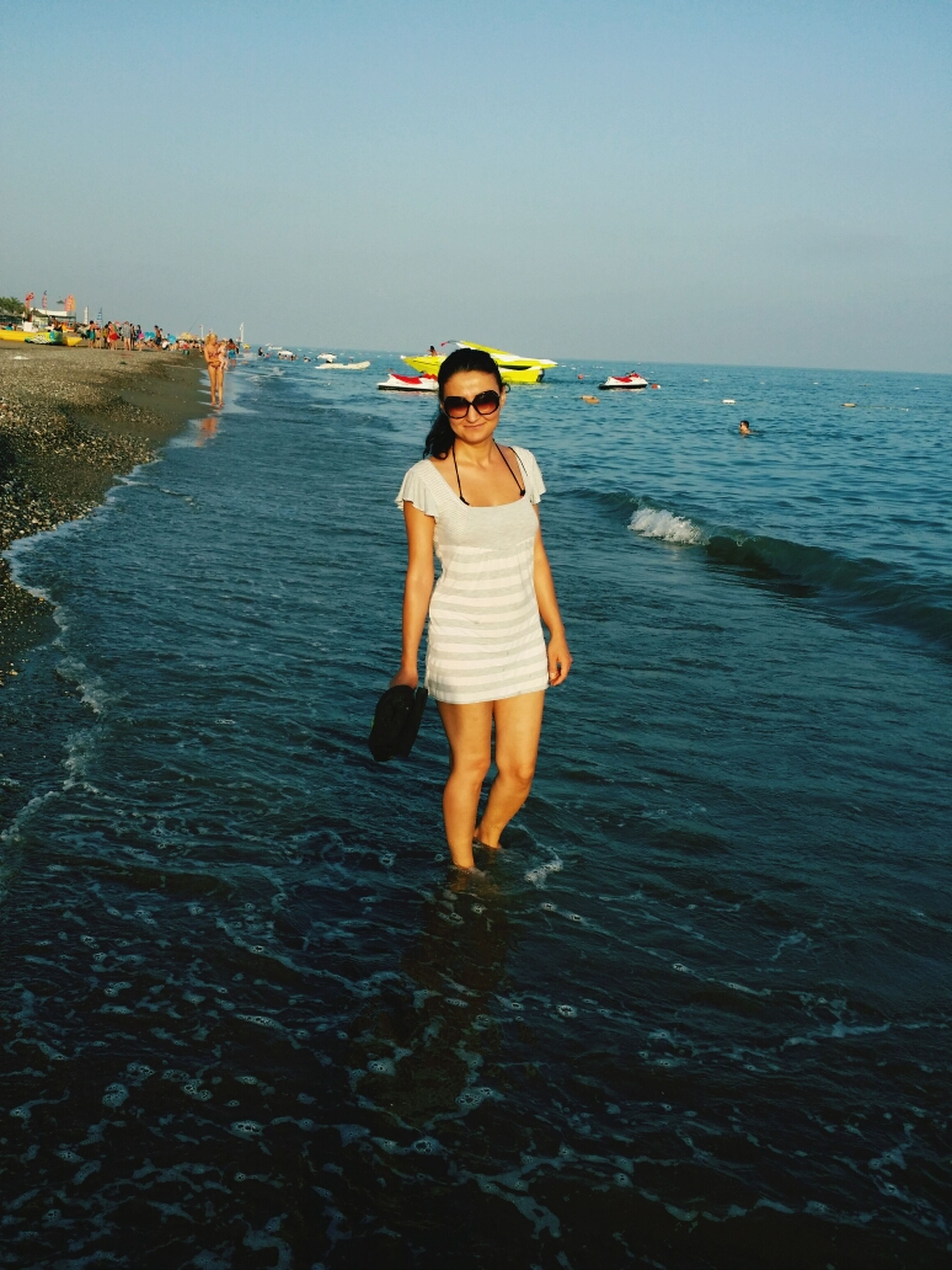 water, full length, sea, leisure activity, lifestyles, casual clothing, beach, clear sky, standing, rear view, horizon over water, childhood, shore, tranquility, person, copy space, tranquil scene, vacations