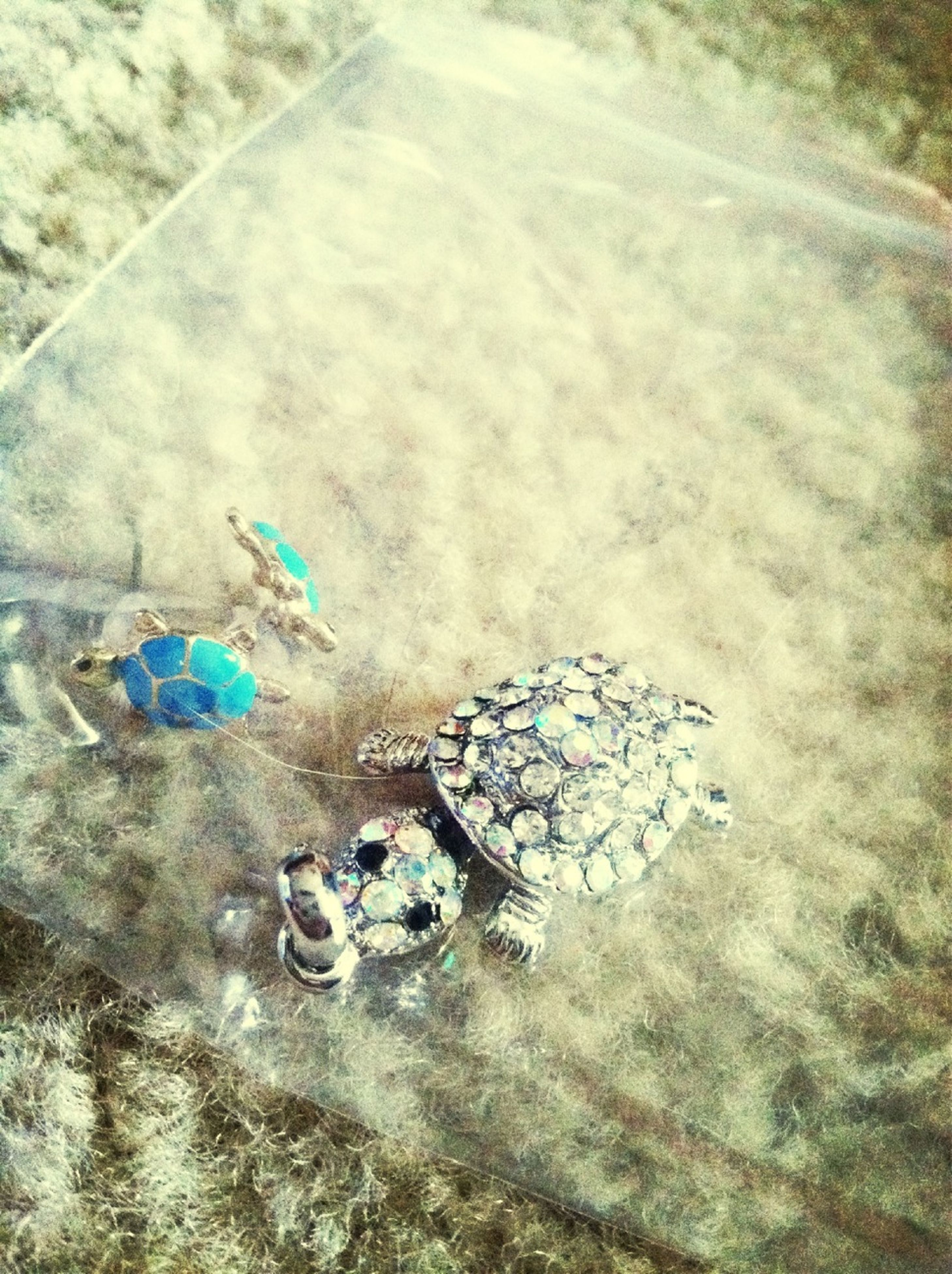 high angle view, transportation, day, creativity, no people, art and craft, outdoors, multi colored, water, blue, art, directly above, nature, pattern, street, sand, bicycle, still life, circle, sunlight