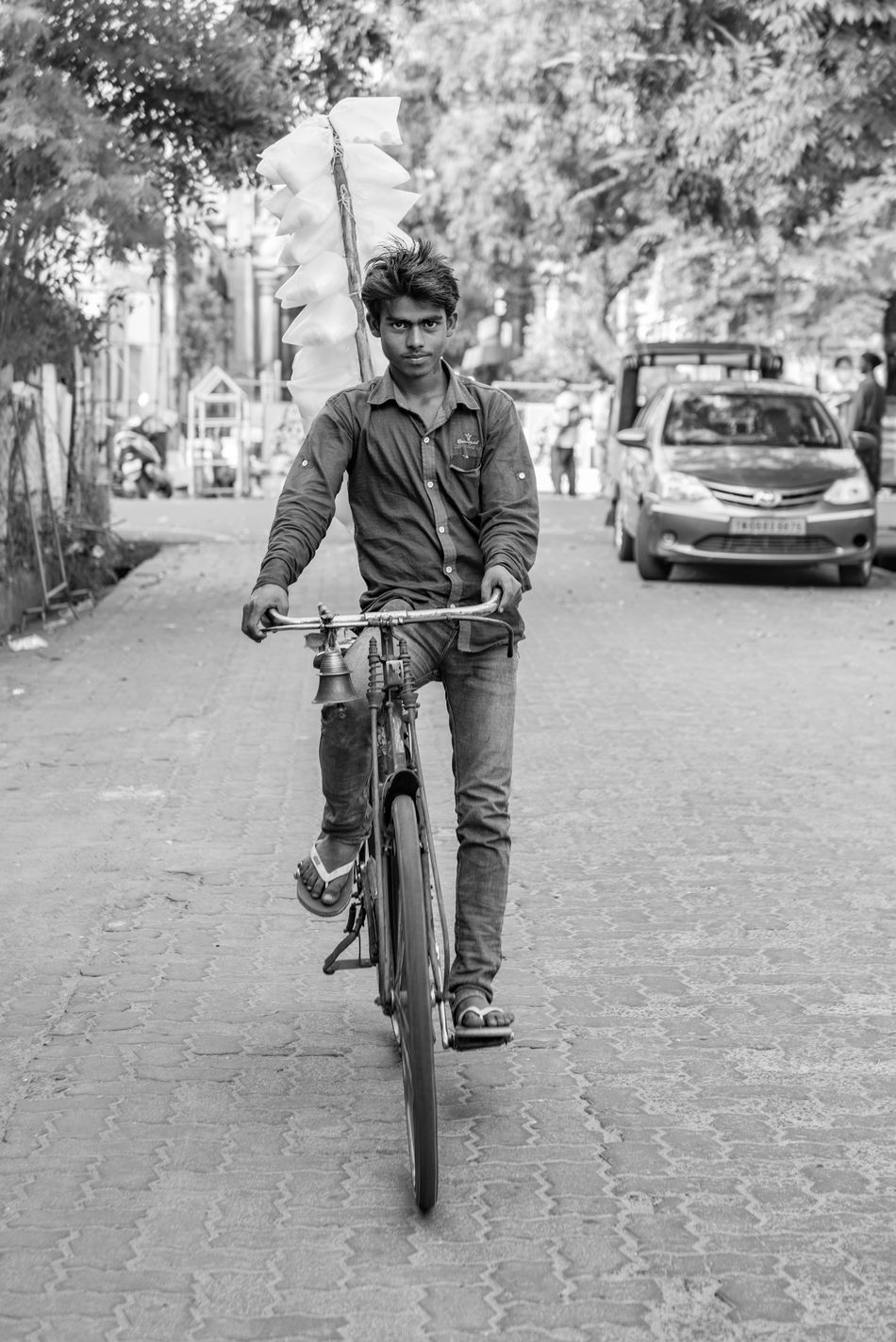 """Portrait of a candy man. On the streets of old Pondi, it is common to see young men trying to sell cotton candy displayed on their bikes. They will try to sweet talk you into buying their sugar while cycling from street to street. (Nikon D810 24-70mm f/2.8 ƒ/3.2 50mm 1/160"""" iso 200) Black And White Candy Cycling Editorial  India Journey Man Portrait Streetphotography Travel"""