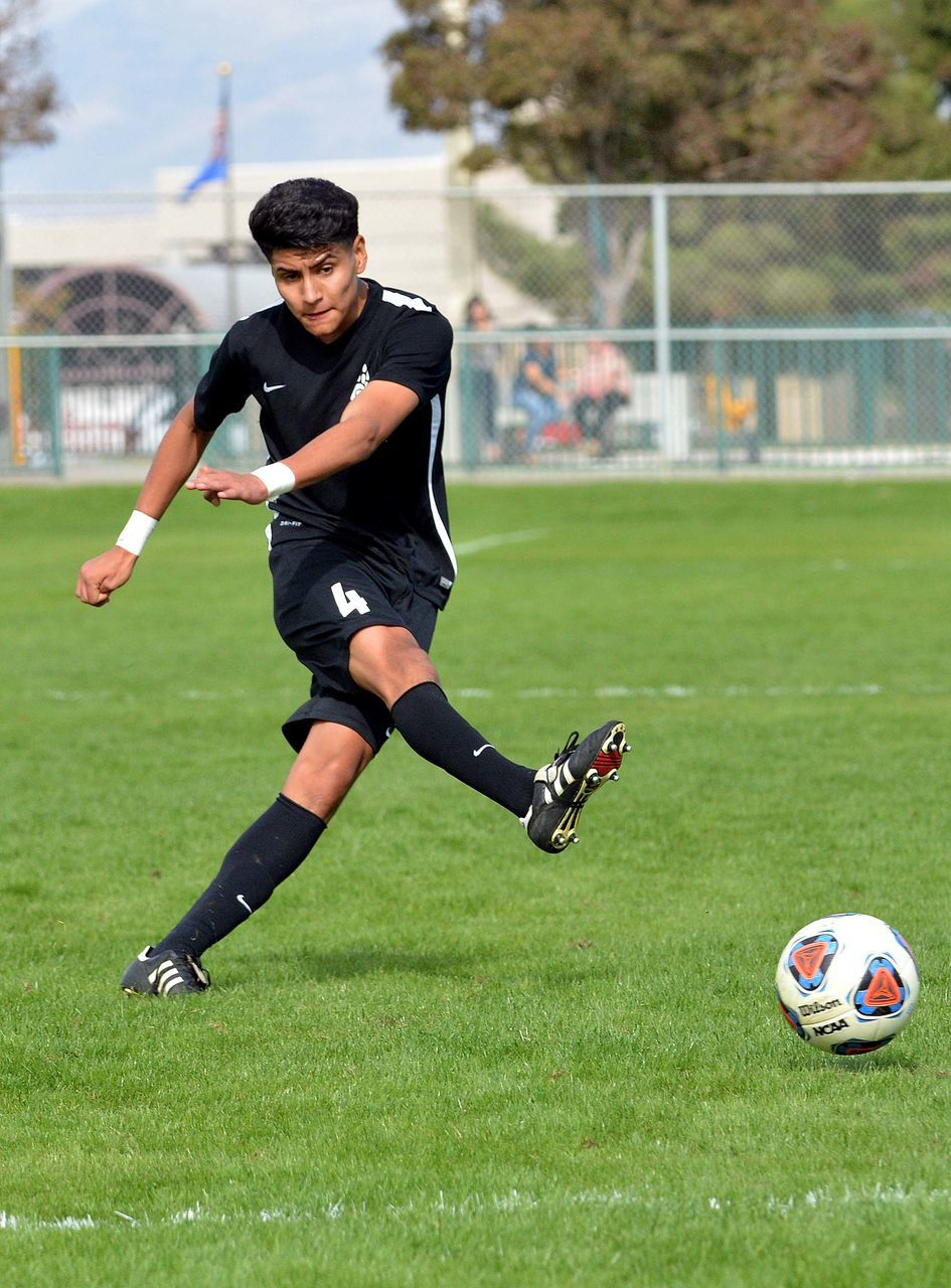 soccer, soccer player, playing, grass, sport, soccer ball, soccer field, sports clothing, soccer uniform, full length, real people, green color, sports uniform, ball, lifestyles, kicking, one person, outdoors, day, young adult, competition, sportsman, competitive sport, athlete, sports team, people