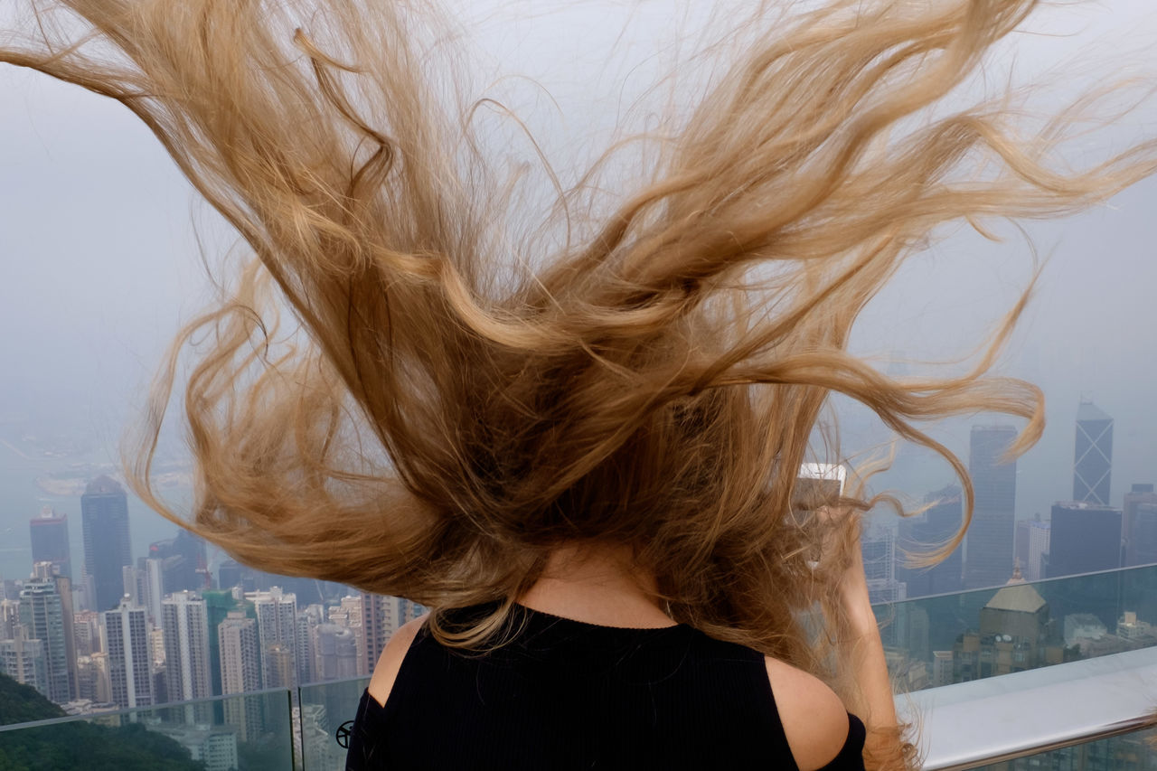 long hair, human hair, one person, blond hair, real people, wind, lifestyles, motion, leisure activity, built structure, tangled hair, day, outdoors, young women, women, young adult, building exterior, architecture, adult, people