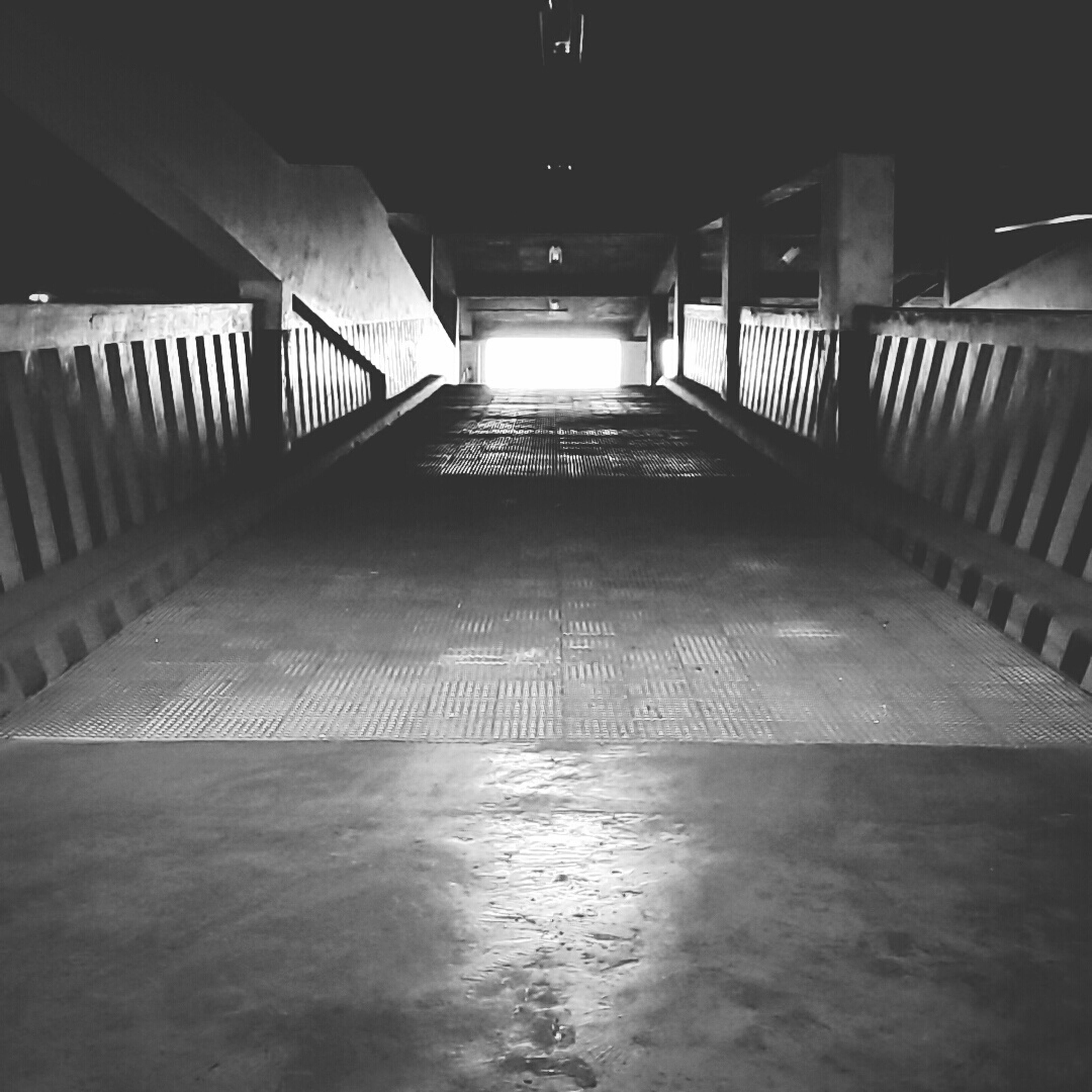 the way forward, railing, built structure, indoors, diminishing perspective, architecture, illuminated, vanishing point, empty, bridge - man made structure, narrow, connection, long, sunlight, walkway, transportation, absence, shadow, steps and staircases, night