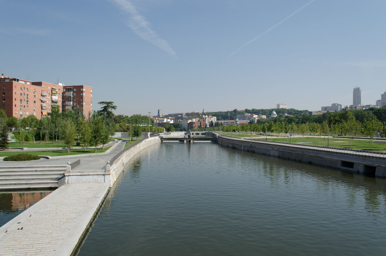 architecture, built structure, building exterior, water, sky, river, outdoors, day, waterfront, no people, tree, nature, city, vapor trail