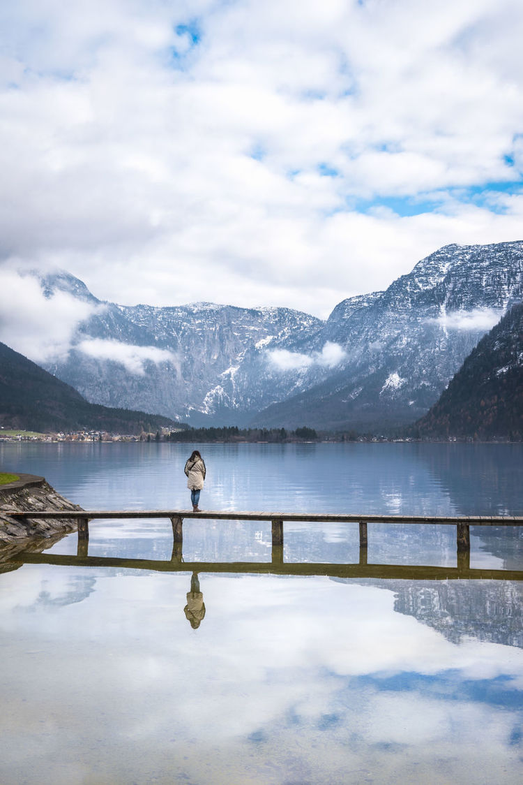 Zen moments theme image with a woman standing alone on a bridge over the Hallstatter lake, surrounded by silence and the Dachstein mountains, in Austria. Austrian Alps Hallstätter See Water Reflections Cold Temperature Hallstatt Hallstatt, Austria Hallstattersee Landscape Mountain Mountain Range Scenics Snow Snowcapped Mountain Tranquility Water Reflection Weather Winter Young Woman Zen Moment