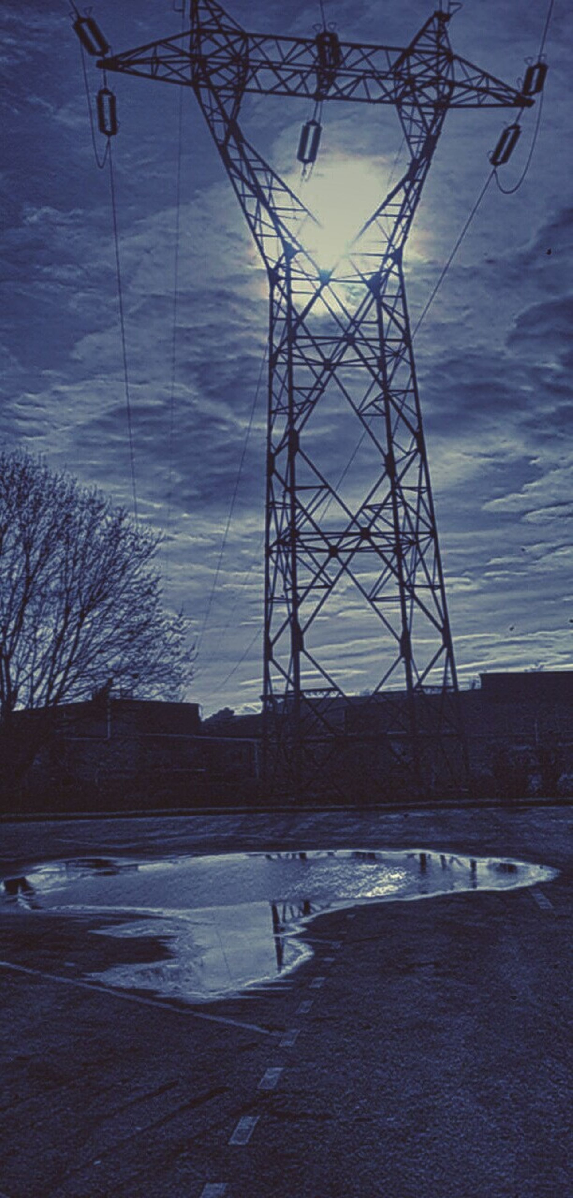 bare tree, electricity pylon, built structure, sky, power line, connection, architecture, electricity, power supply, water, silhouette, cable, building exterior, no people, tree, outdoors, street, low angle view, sunlight, cloud - sky