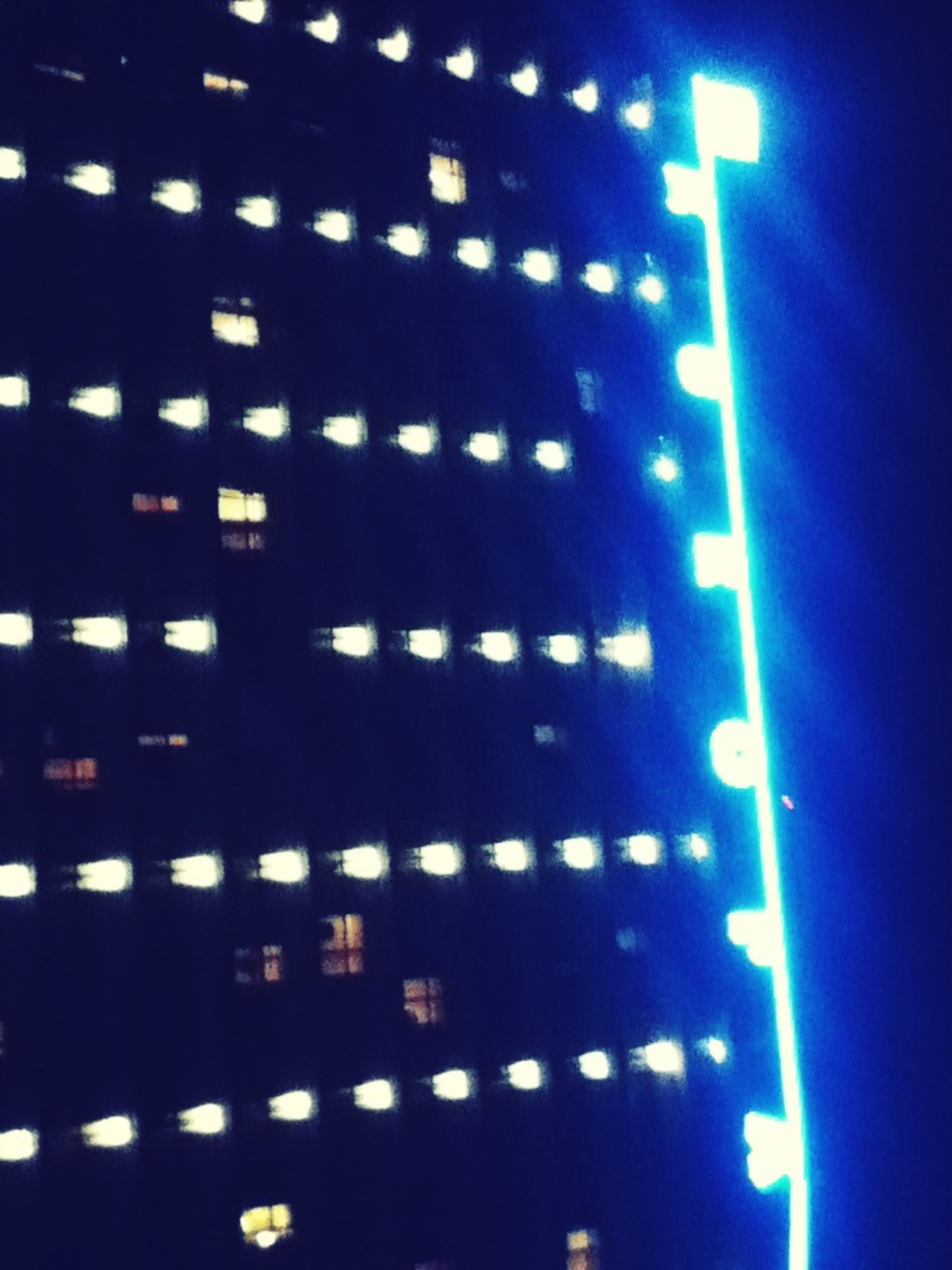 illuminated, night, indoors, lighting equipment, architecture, built structure, low angle view, light - natural phenomenon, pattern, glowing, in a row, building, repetition, modern, electric light, light, no people, building exterior, reflection, window
