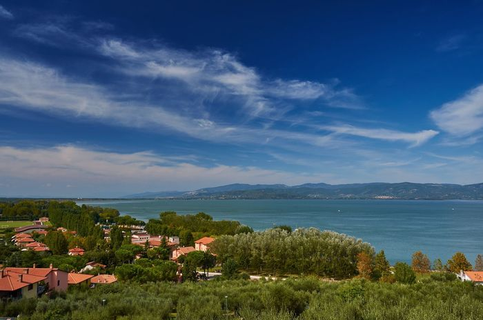 Lago Trasimeno seen from the town of Castiglione del Lago Lago Trasimeno Lake Trasimeno Lake Lake View Italy Umbria Castiglione Del Lago Blue Sky Clouds And Sky Nature Landscape Lakeside Lakeshore Water Beauty In Nature No People Outdoors Day Town Village Trees Rooftops