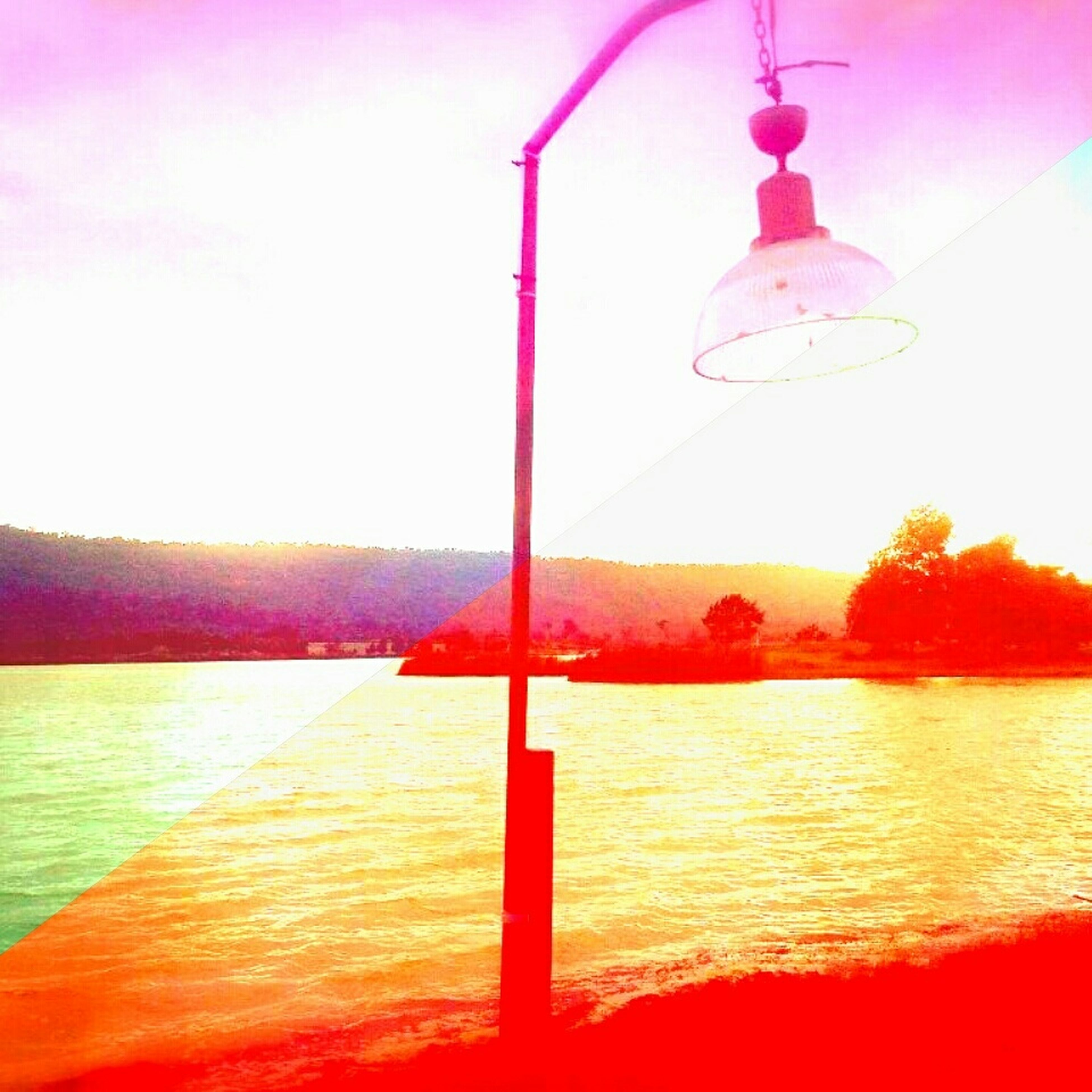 lighting equipment, water, red, tranquility, reflection, tranquil scene, sunset, orange color, street light, sky, no people, nature, scenics, lake, beauty in nature, clear sky, outdoors, idyllic, electric light, day
