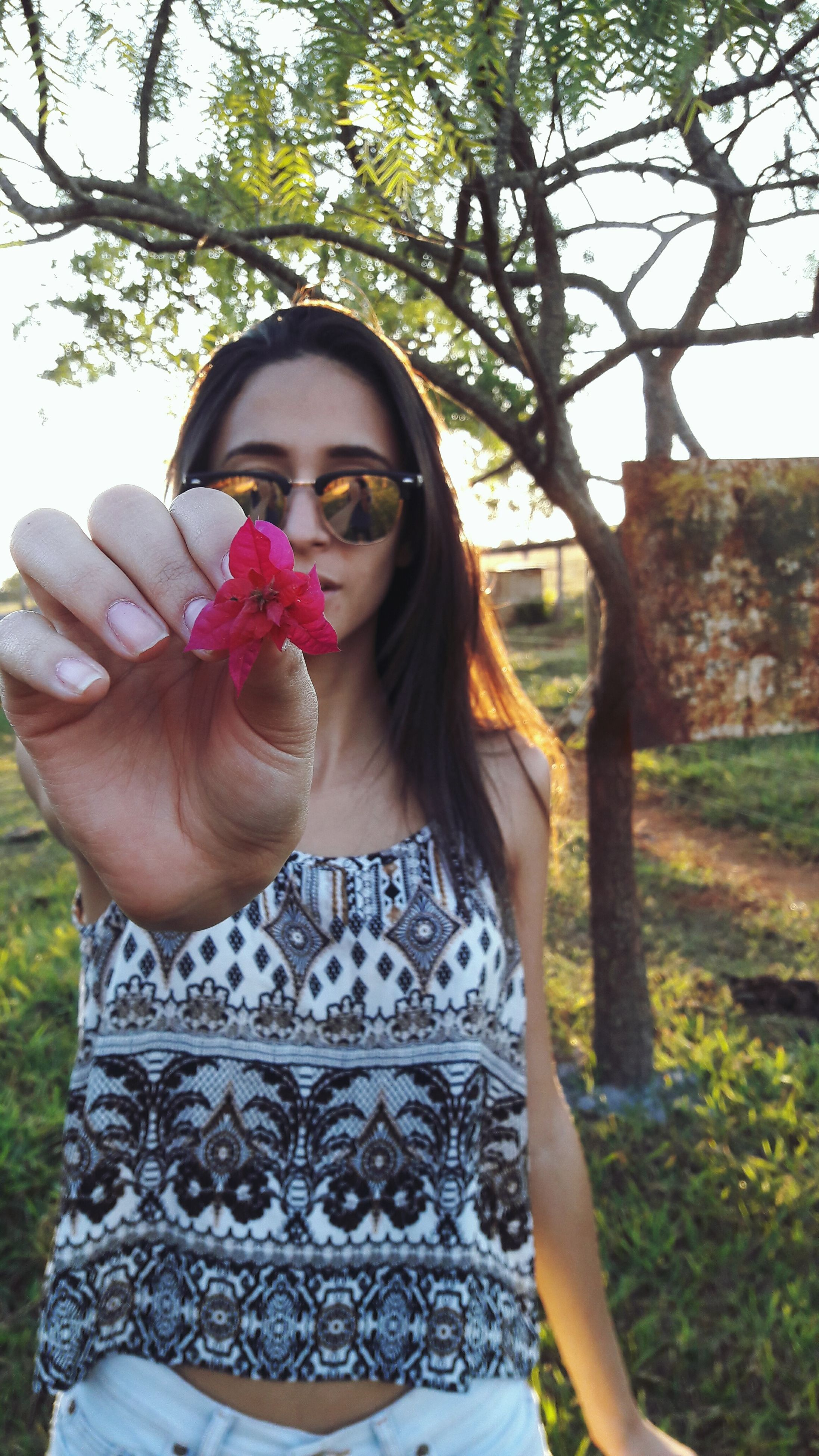 lifestyles, person, young adult, leisure activity, holding, front view, portrait, casual clothing, young women, looking at camera, flower, tree, freshness, standing, sunglasses, smiling, headshot, day