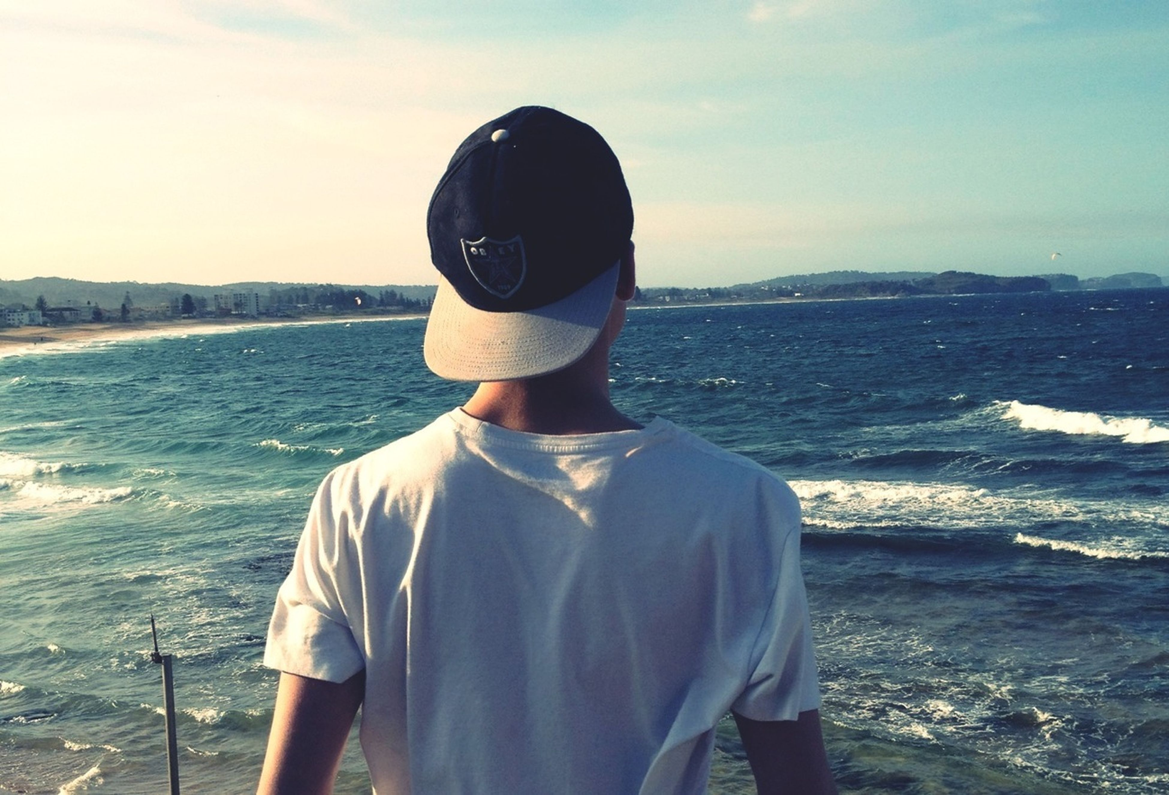 rear view, sea, water, standing, lifestyles, leisure activity, sky, casual clothing, waist up, three quarter length, tranquil scene, tranquility, looking at view, men, scenics, beach, beauty in nature, nature