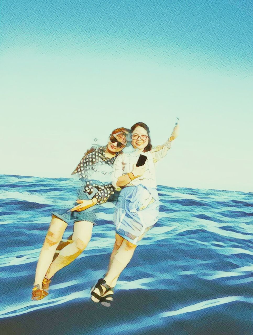 sea, water, smiling, happiness, full length, real people, young women, young adult, horizon over water, two people, leisure activity, vacations, clear sky, lifestyles, looking at camera, outdoors, beach, nature, day, beauty in nature, blue, cheerful, selfie, portrait, togetherness, sky, beautiful woman, photography themes