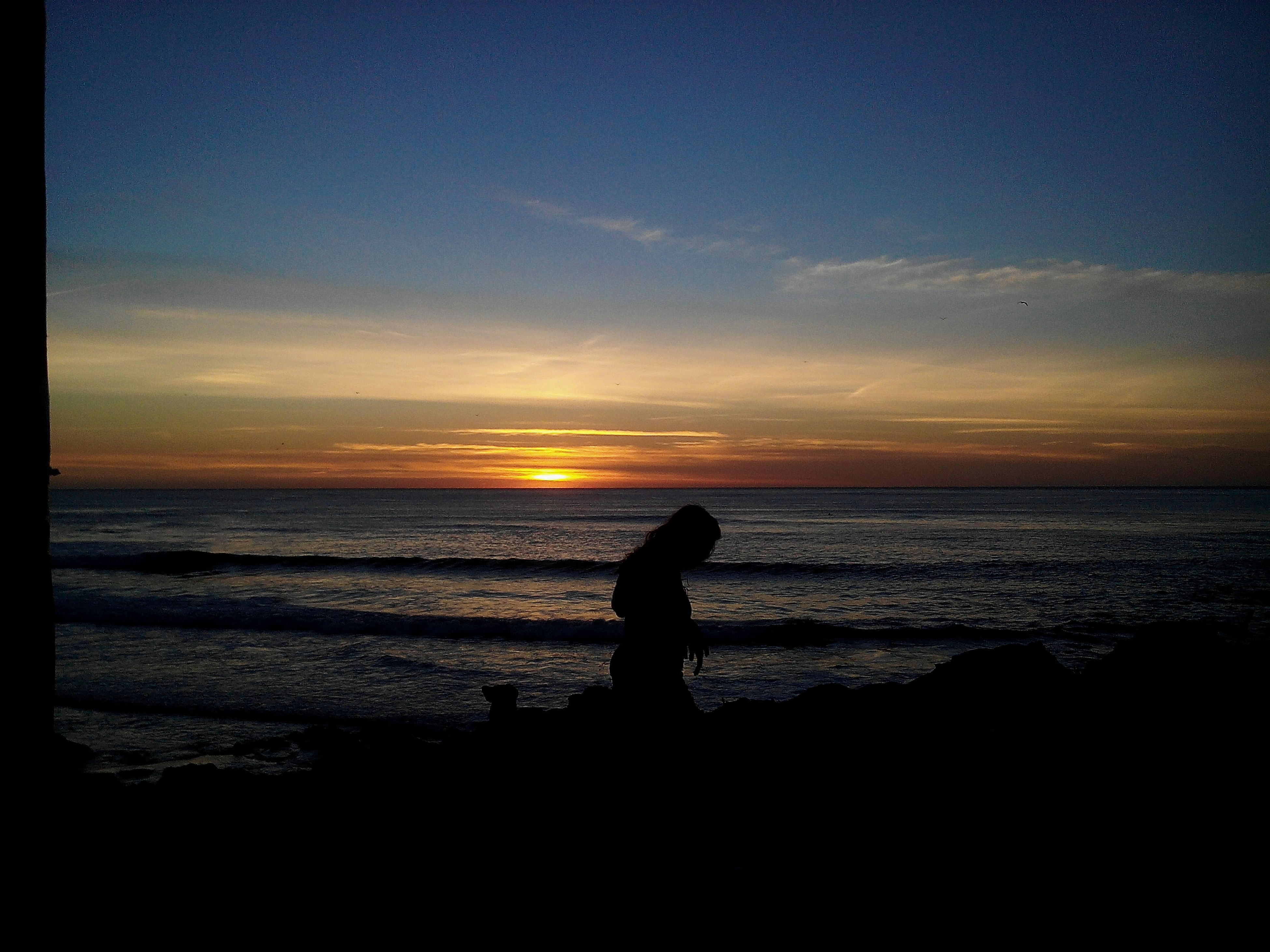 sunset, silhouette, sea, scenics, beauty in nature, tranquil scene, water, tranquility, orange color, sky, horizon over water, beach, standing, idyllic, shore, nature, men, outline