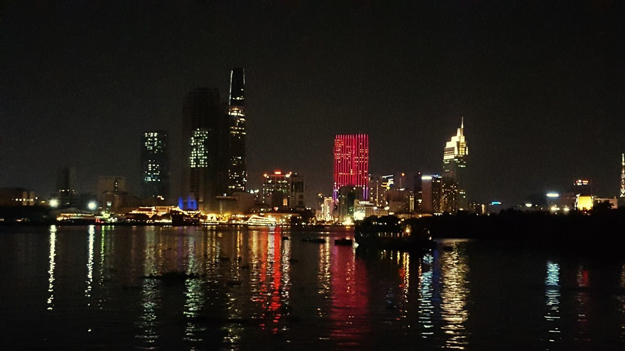 illuminated, night, architecture, building exterior, skyscraper, built structure, waterfront, city, reflection, travel destinations, no people, cityscape, sky, water, outdoors, urban skyline