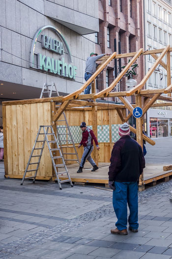Dismantling market stall at Munich Christmas market in Marienplatz, Germany. Christmas Christmas Market Dismantling Architecture Building Exterior Built Structure Day Editorial  End Full Length Lifestyles Men Outdoors People Real People Rear View Stall Standing Two People