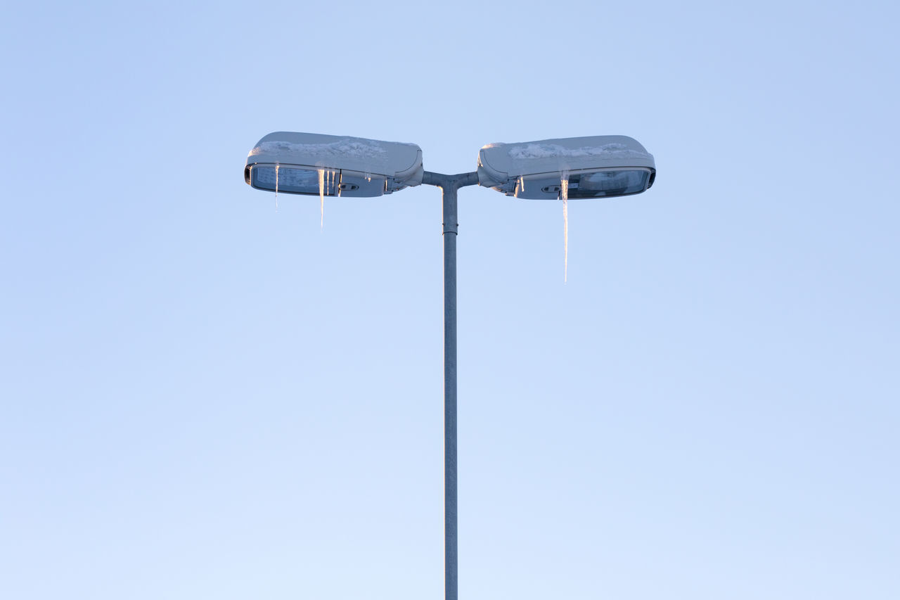Street lights with icicles against clear blue sky Blue Clear Sky Cold Temperature Copy Space Day Dusk Electric Lamp Electric Light Frozen Ice Icicle In The Center Lighting Equipment Low Angle View No People Outdoors Polar Climate Simplicity Street Light Symmetry Weather Winter