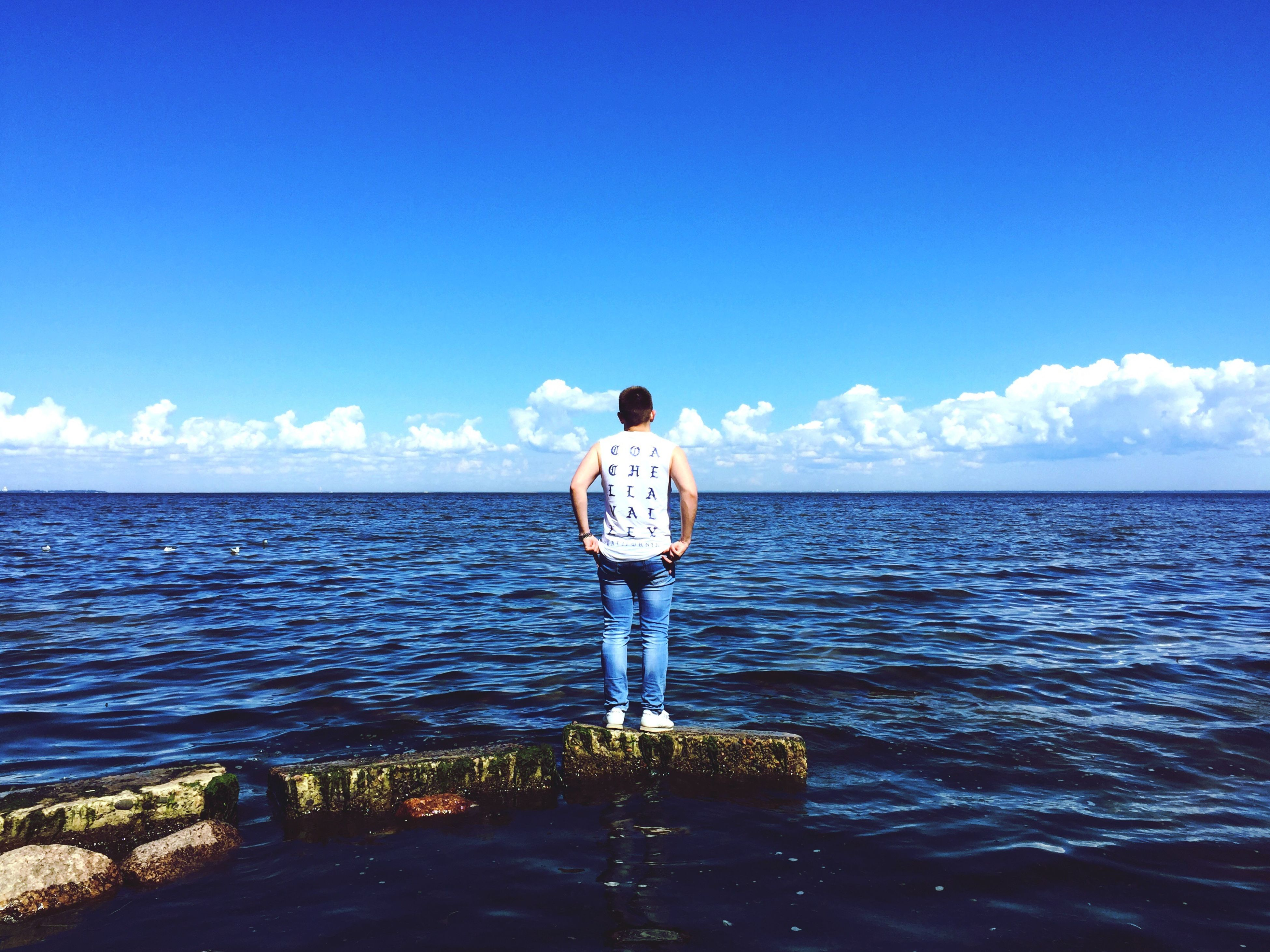 sea, horizon over water, water, nature, sky, real people, one person, rear view, standing, full length, scenics, tranquil scene, casual clothing, beauty in nature, outdoors, day, cloud - sky, tranquility, leisure activity, men, lifestyles, young adult