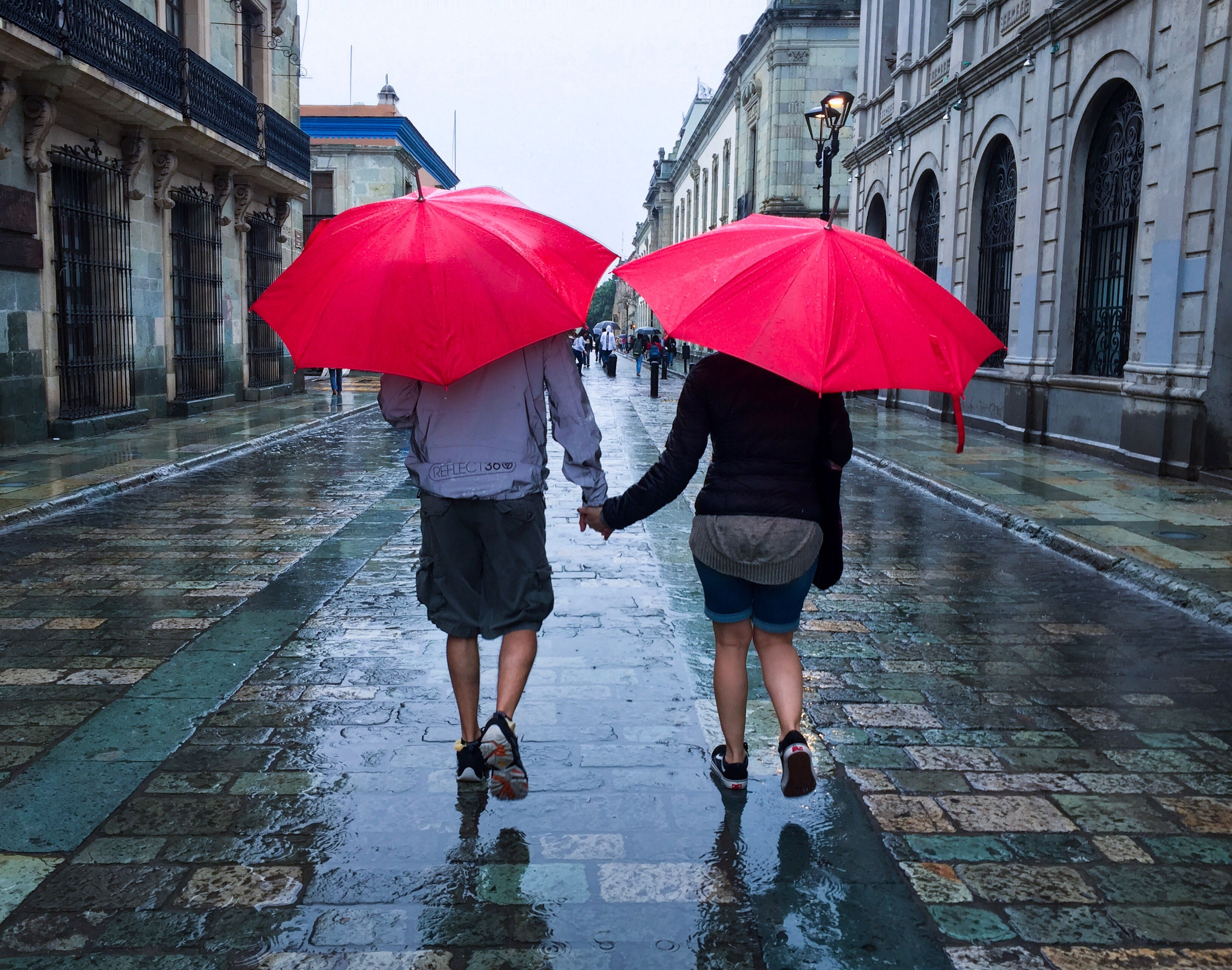 rain, wet, rainy season, weather, protection, togetherness, two people, friendship, real people, rear view, walking, raindrop, full length, water, love, bonding, outdoors, lifestyles, day, architecture, under, city, adult, people