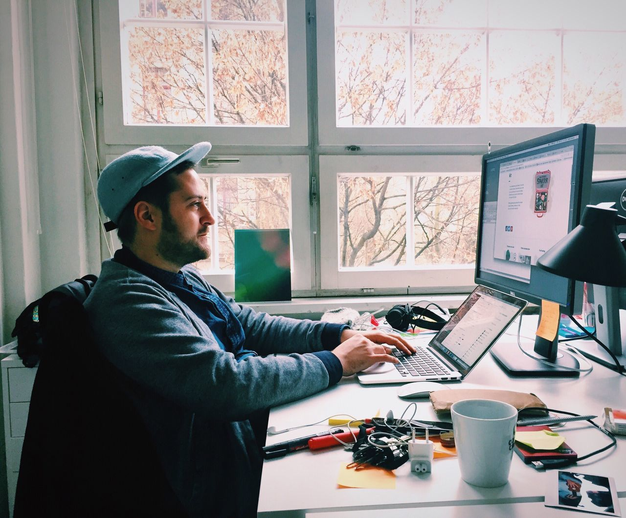 Focused designer using laptop in office Waist Up Window One Person Indoors  Desk Technology One Man Only Real People Working Men Workshop Only Men Adults Only Day Adult People Business Startup Designer  Office Working