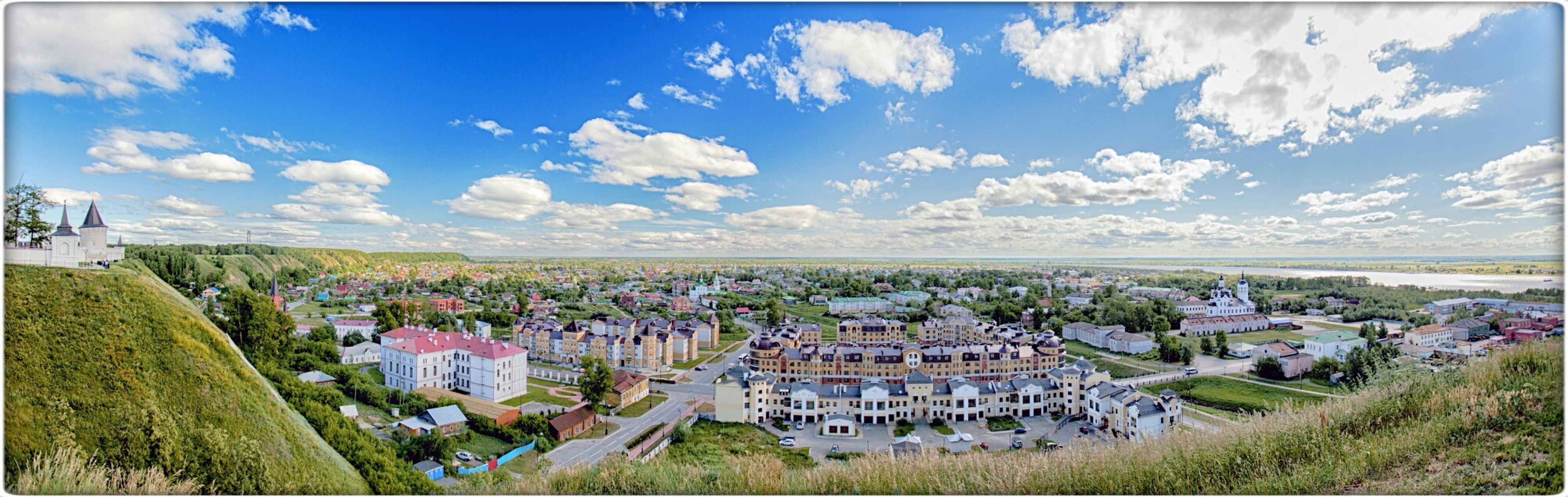 building exterior, architecture, built structure, sky, house, tree, cloud - sky, town, cloud, landscape, residential structure, panoramic, blue, city, field, residential district, high angle view, townscape, grass, village