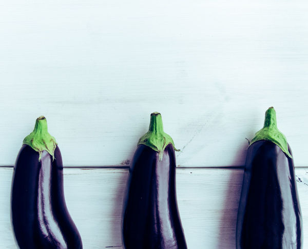 Three fresh healthy eggplants on white wooden background. Additional space for text. Agriculture Arranged Objects Aubergine Copy Space Diet Eggplant Fresh Gluten Free Healthy Lifestyle Kitchen Table Lines Minimalism Organic Food Organic Living Ripe Still Life Top View Of Food White Texture Wooden Texture
