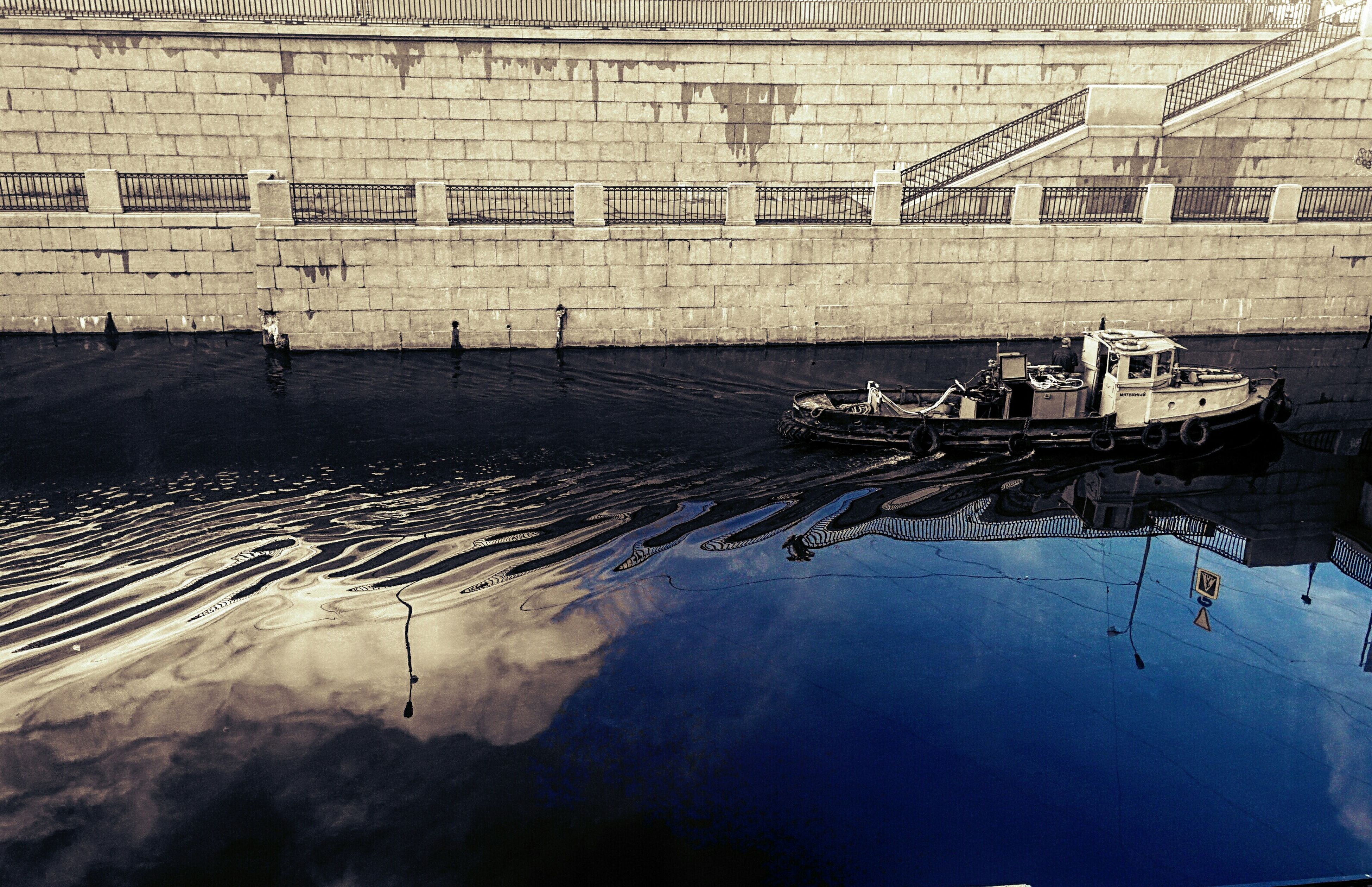 water, text, built structure, architecture, reflection, western script, communication, building exterior, nautical vessel, transportation, outdoors, day, sea, mode of transport, wet, no people, waterfront, wall - building feature, high angle view, boat