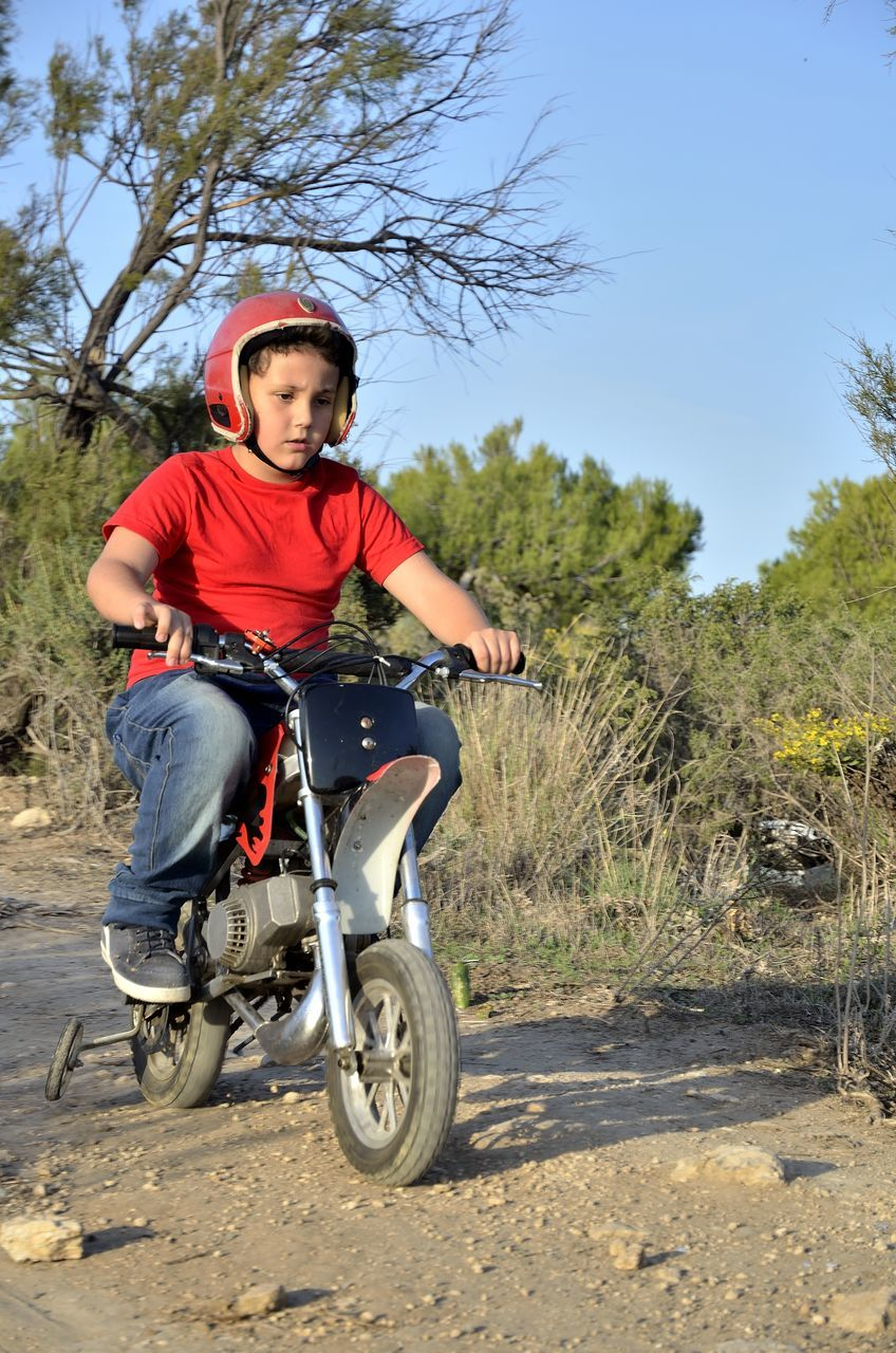 Boy Riding Motorcycle On Dirt Road