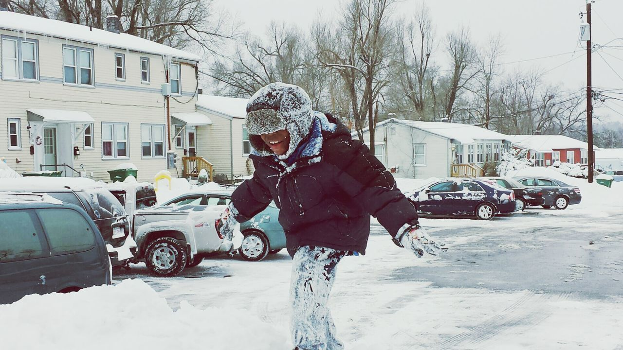 Man Standing On Snow Covered Street By Houses