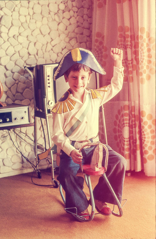 Boy Child Childhood Costume CostumeParty Home Horse Toy Indoors  Kid Leisure Lifestyles Living Room Livingroom Looking At Camera Posing Real People Retro Riding Smiling Soldier Toy Vintage Colors Vintage Photo Warmy Wooden Horse