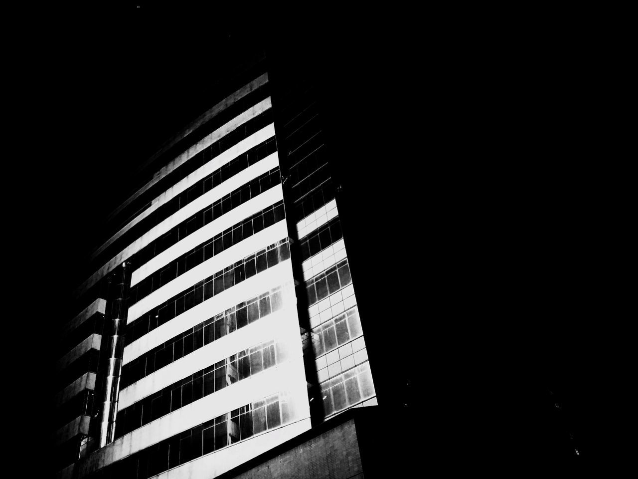 architecture, window, low angle view, building exterior, built structure, modern, illuminated, no people, night, indoors, skyscraper, apartment, city, black background, close-up