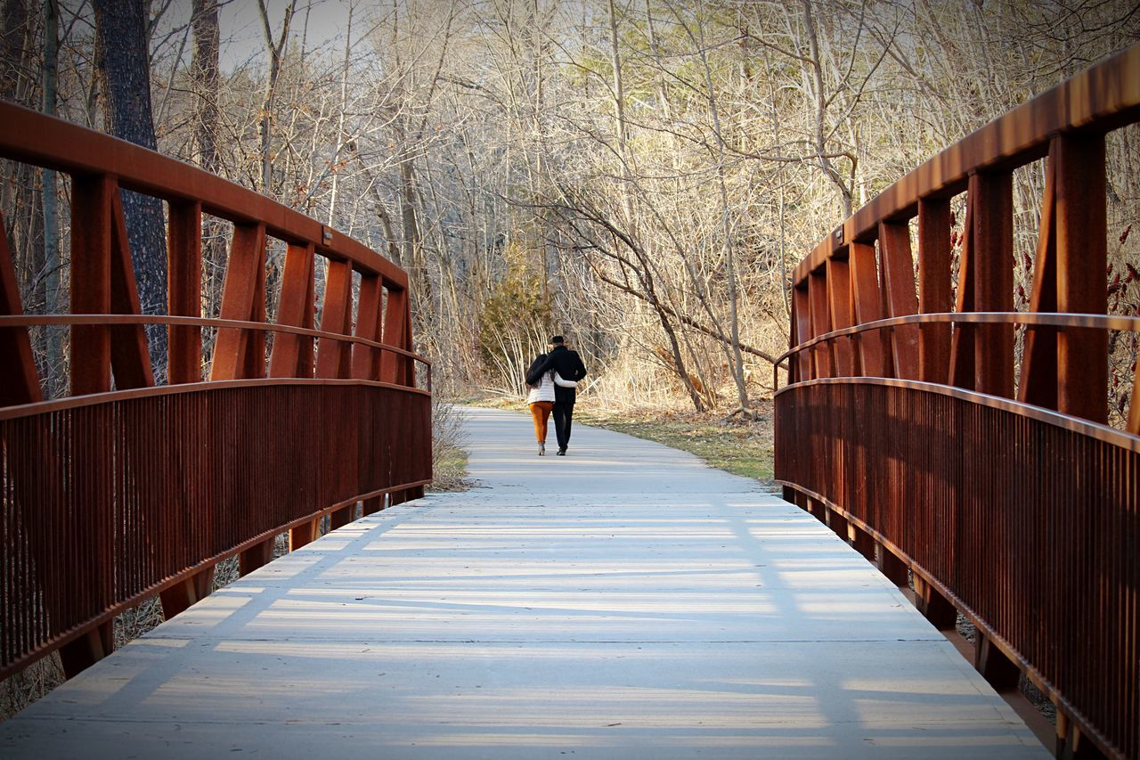 real people, walking, one person, railing, full length, rear view, architecture, winter, built structure, footbridge, the way forward, tree, day, wood - material, bridge - man made structure, lifestyles, outdoors, bare tree, snow, women, wood paneling, nature, warm clothing