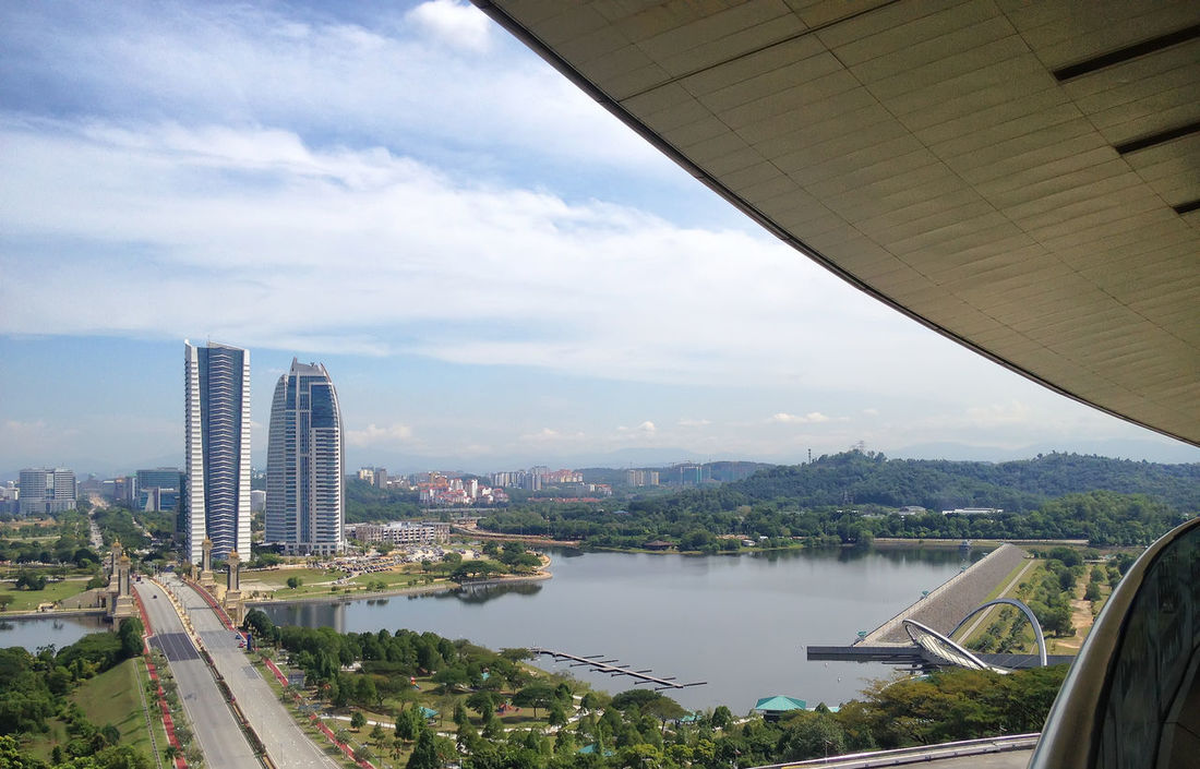 Landscape view of Putrajaya Pullman lakeside and dam from high angle view with white and blue skies during daytime. Architecture Bridge - Man Made Structure Building Exterior Built Structure City Cityscape Cloud - Sky Downtown District Modern No People Outdoors Putrajaya International Convention Center Putrajayaview River Sky Skyscraper Transportation Travel Destinations Urban Skyline Water Waterfront